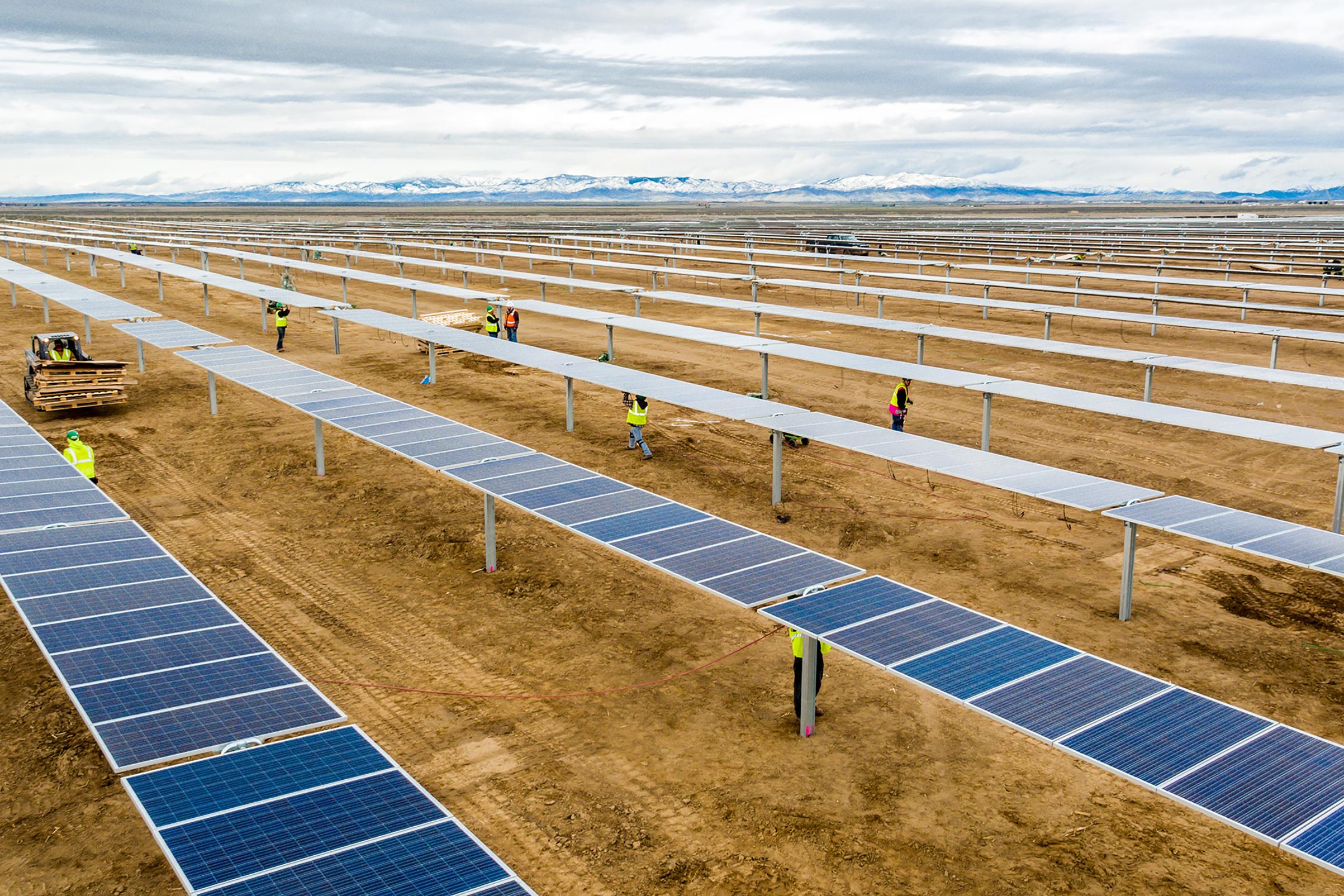 Construction crews assemble solar modules for a 55-megawatt power plant in Idaho built by DEPCOM