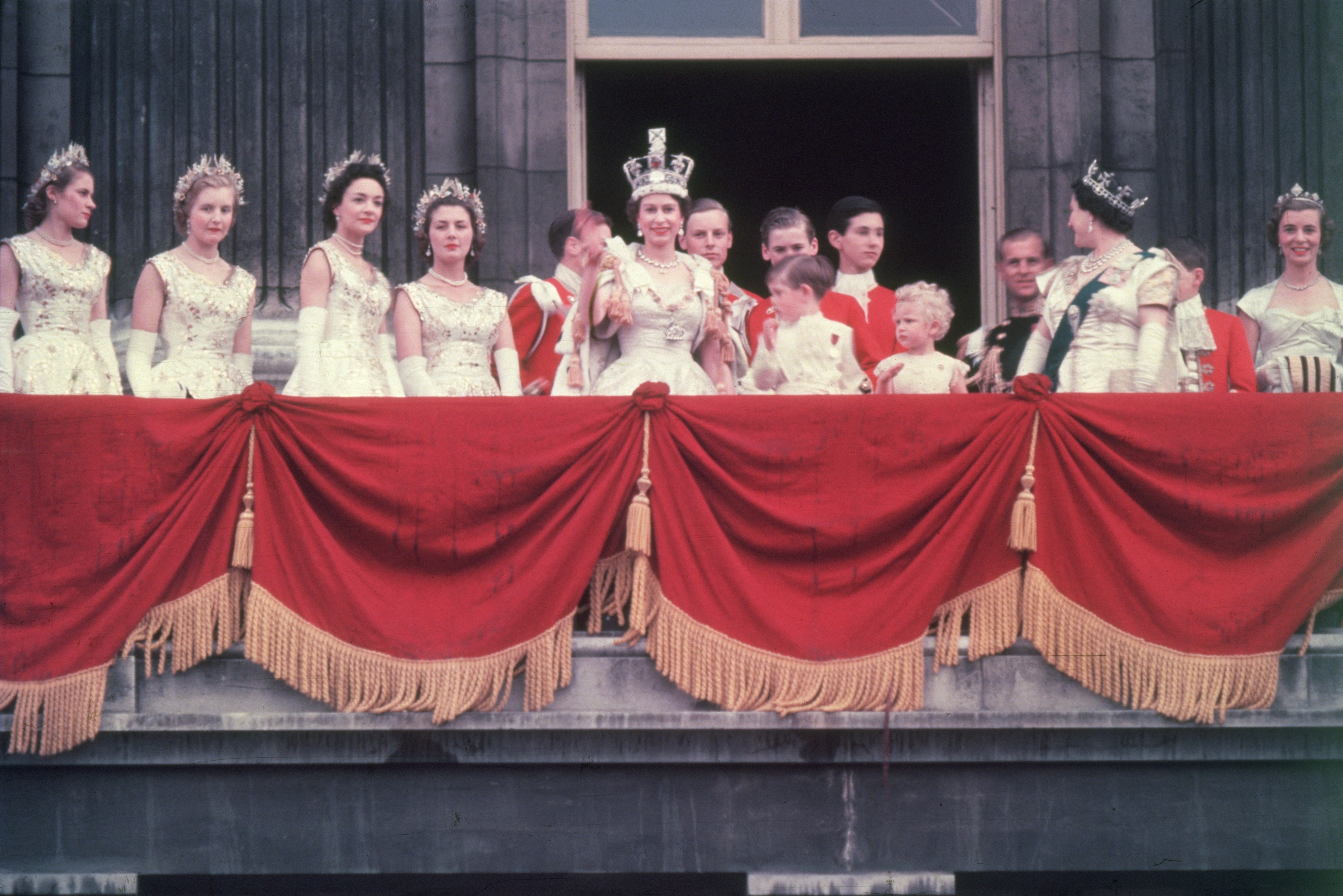 The newly crowned Queen Elizabeth II waves to the crowd from the balcony at Buckingham Palace on June 2, 1953. Her children Prince Charles and Princess Anne stand with her.
