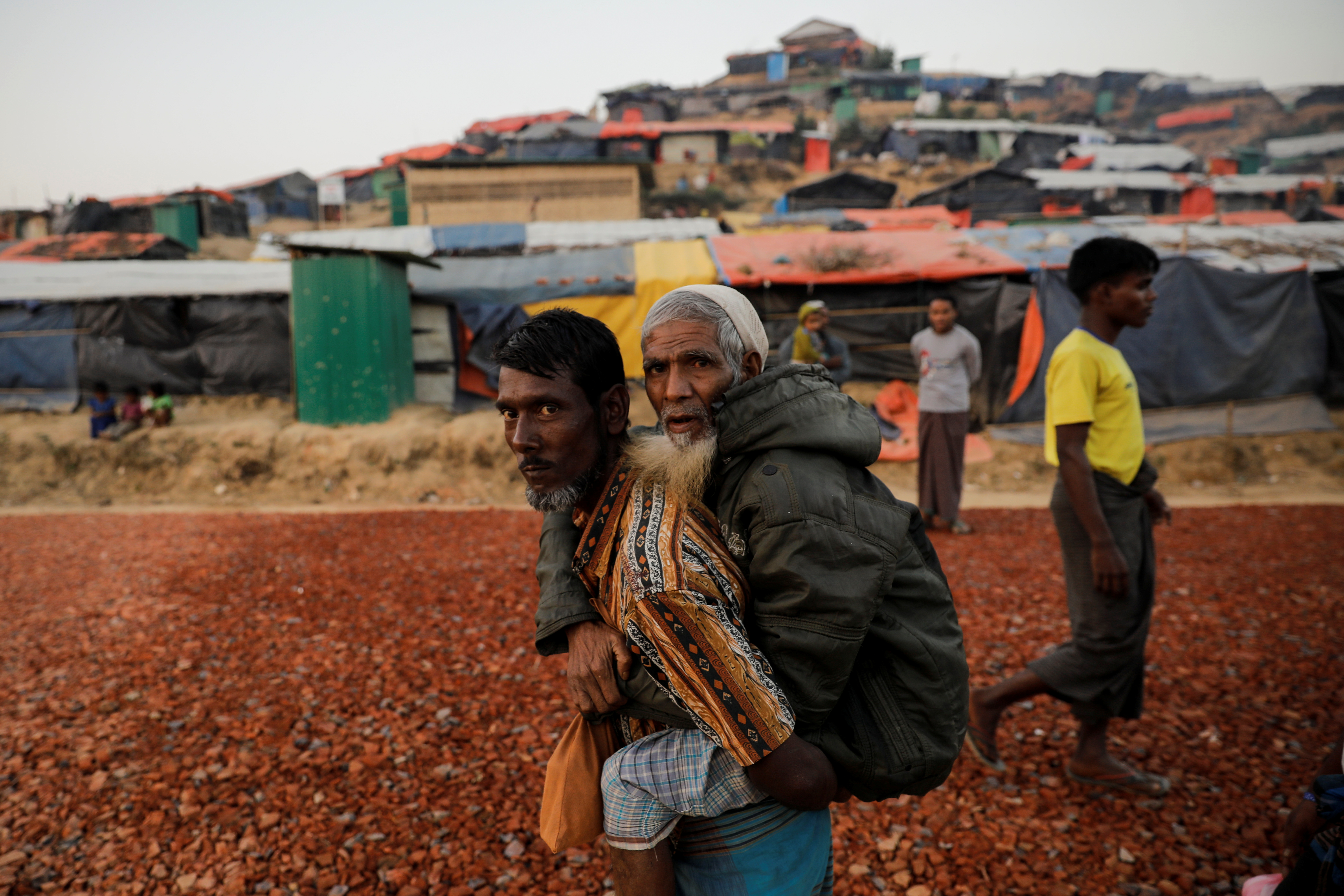 A Rohingya refugee carries an elderly man at the Palongkhali refugee camp near Cox's Bazar, Bangladesh on Dec. 23, 2017.