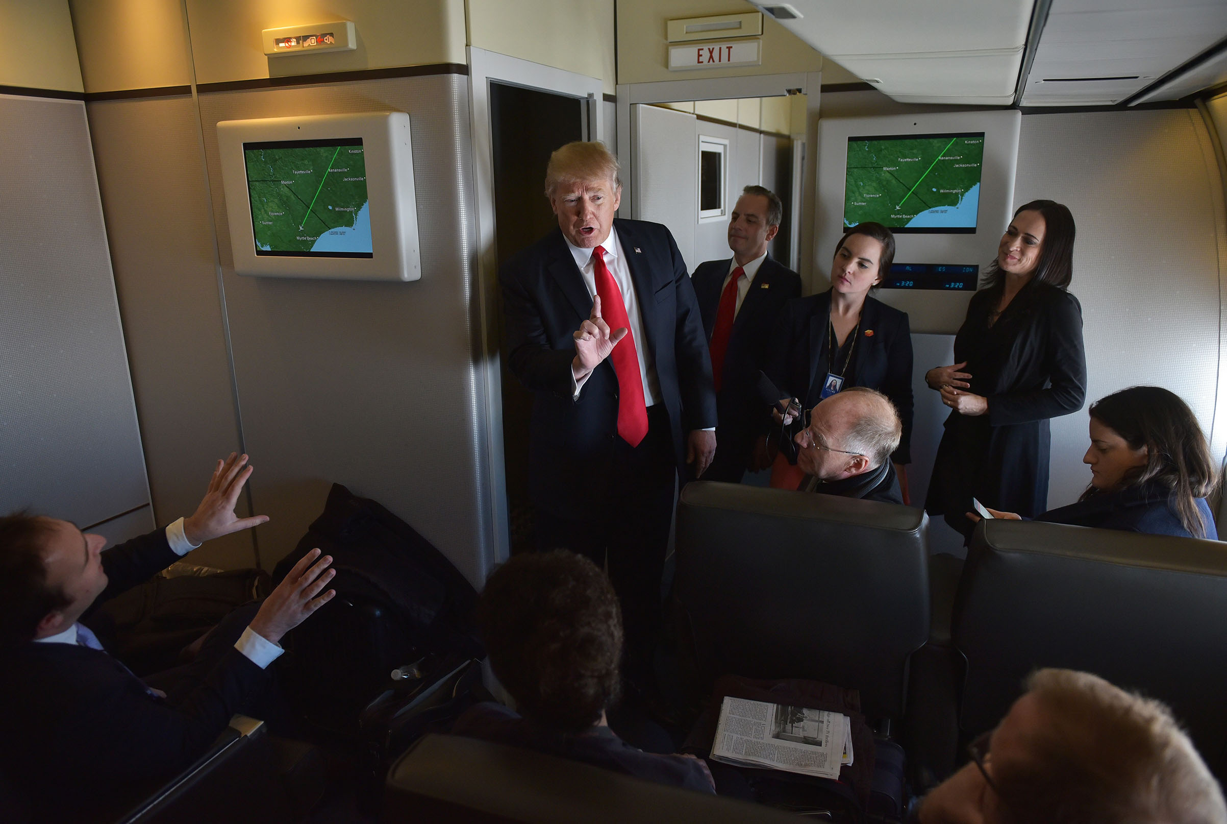 President Donald Trump chats with reporters on board Air Force One before departing from Andrews Air Force Base.