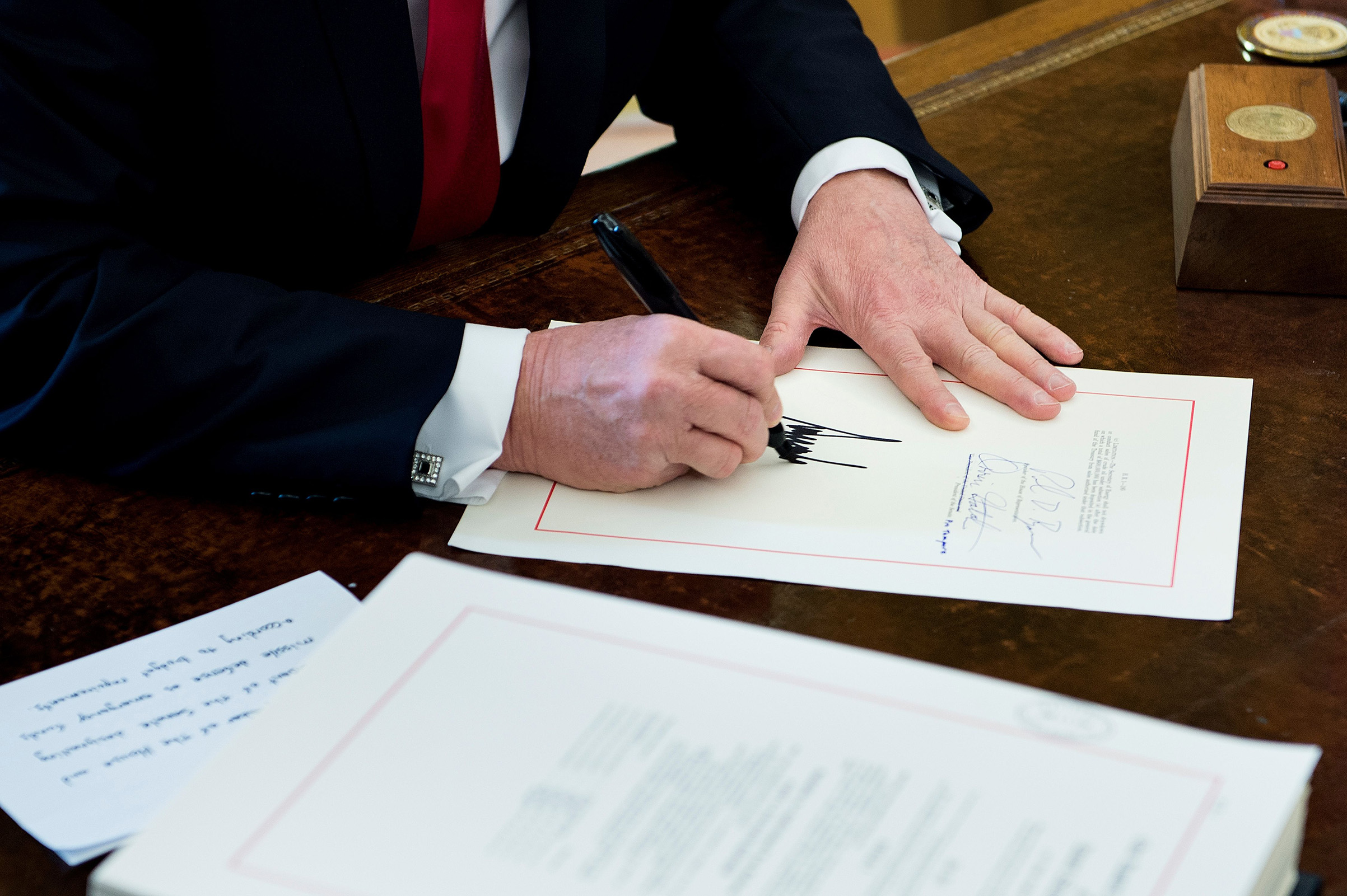 President Donald Trump signs the Tax Cut and Reform Bill in the Oval Office at The White House on Dec. 22, 2017.