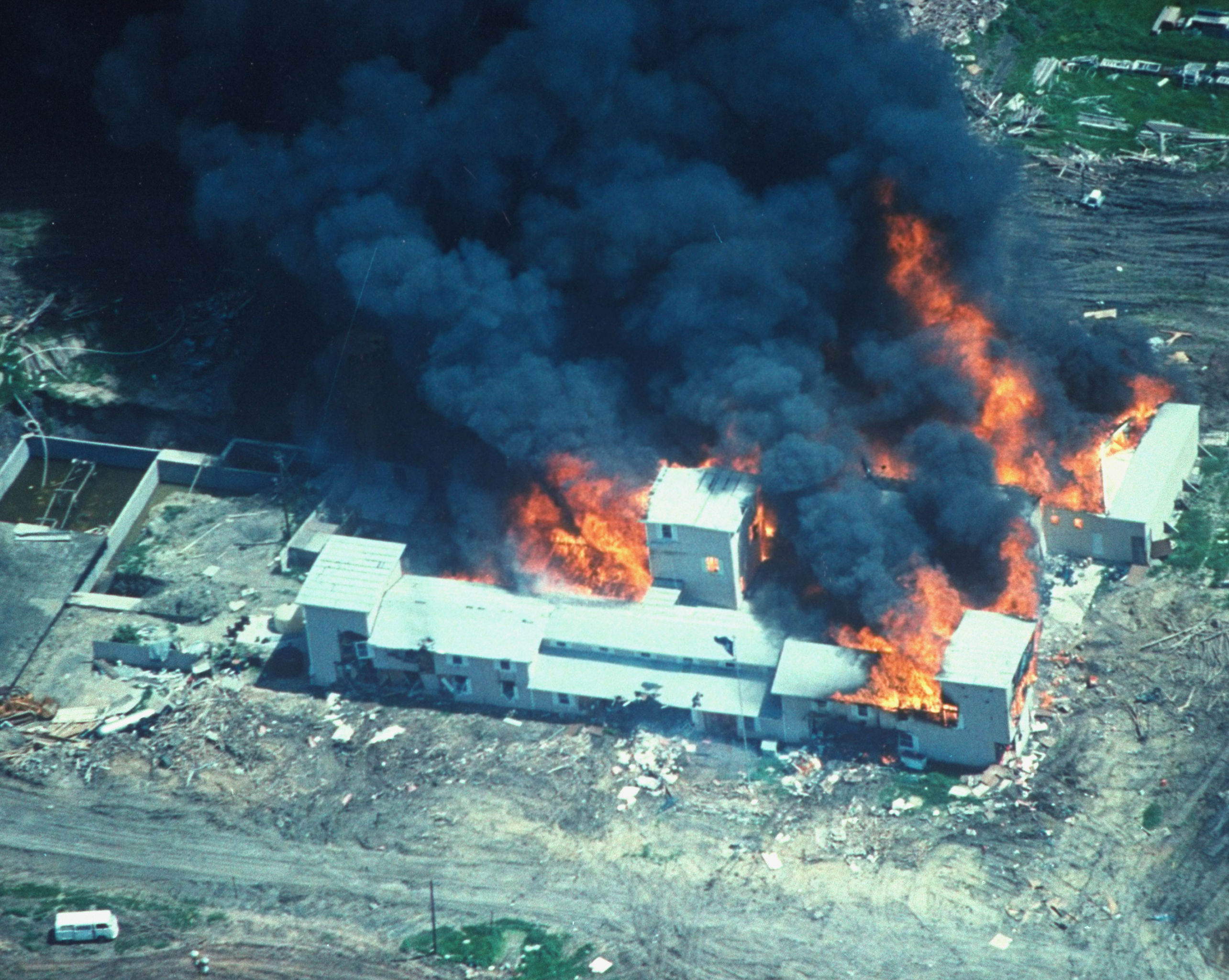 Overhead of smoking fire consuming David Koresh-led Branch Davidian cult compound