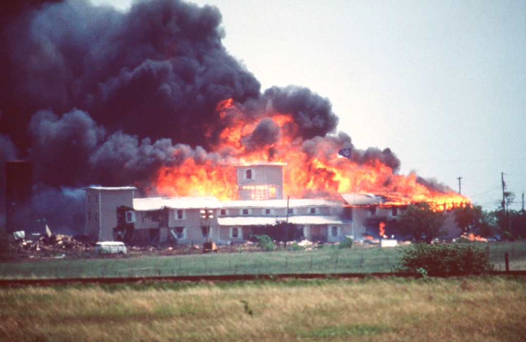 Smoking fire consumes the Branch Davidian Compound during the FBI assault to end the 51-day standoff with cult leader David Koresh and his followers.