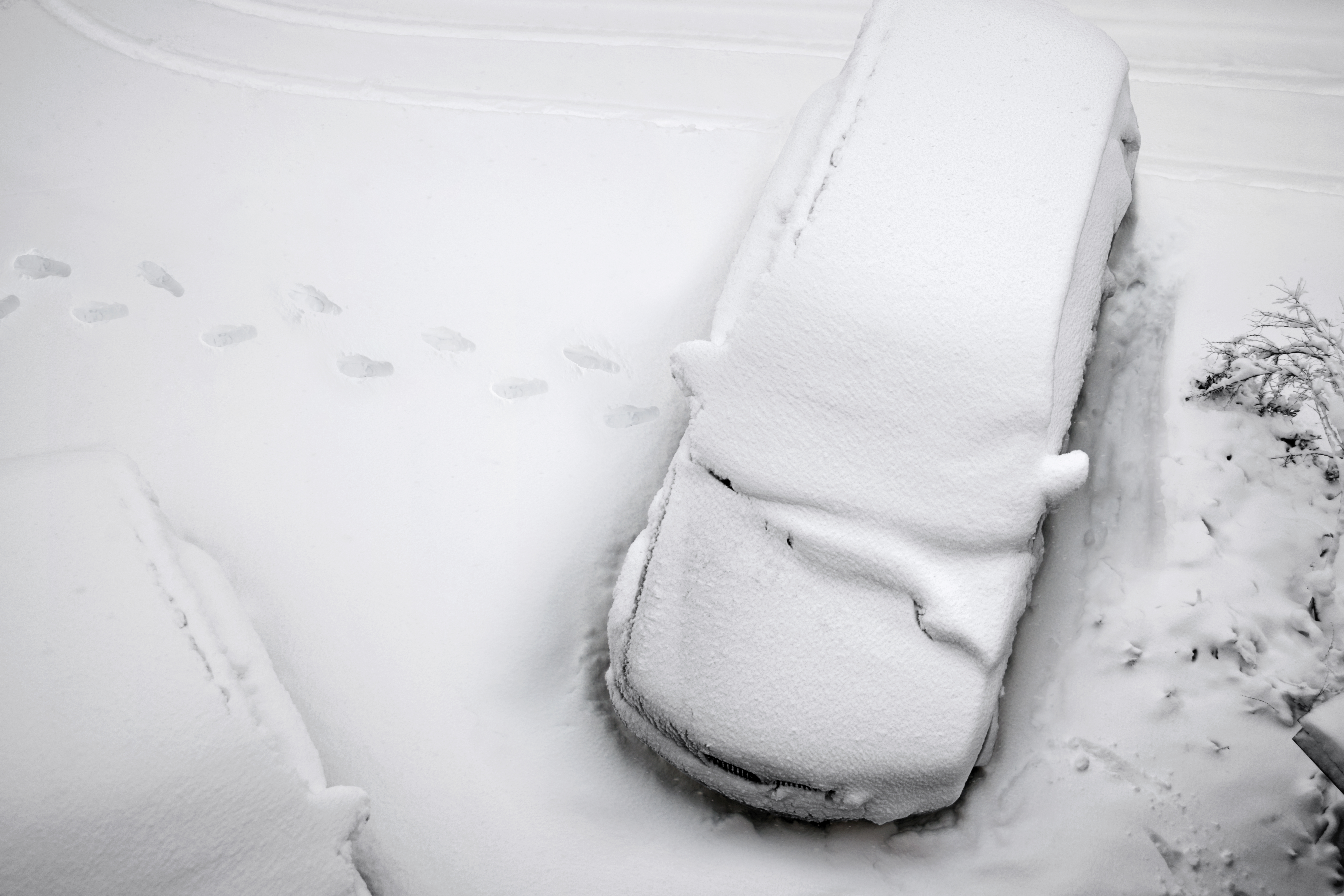 A car abandoned in the snow with foot prints leading away from the abandoned vehicle.