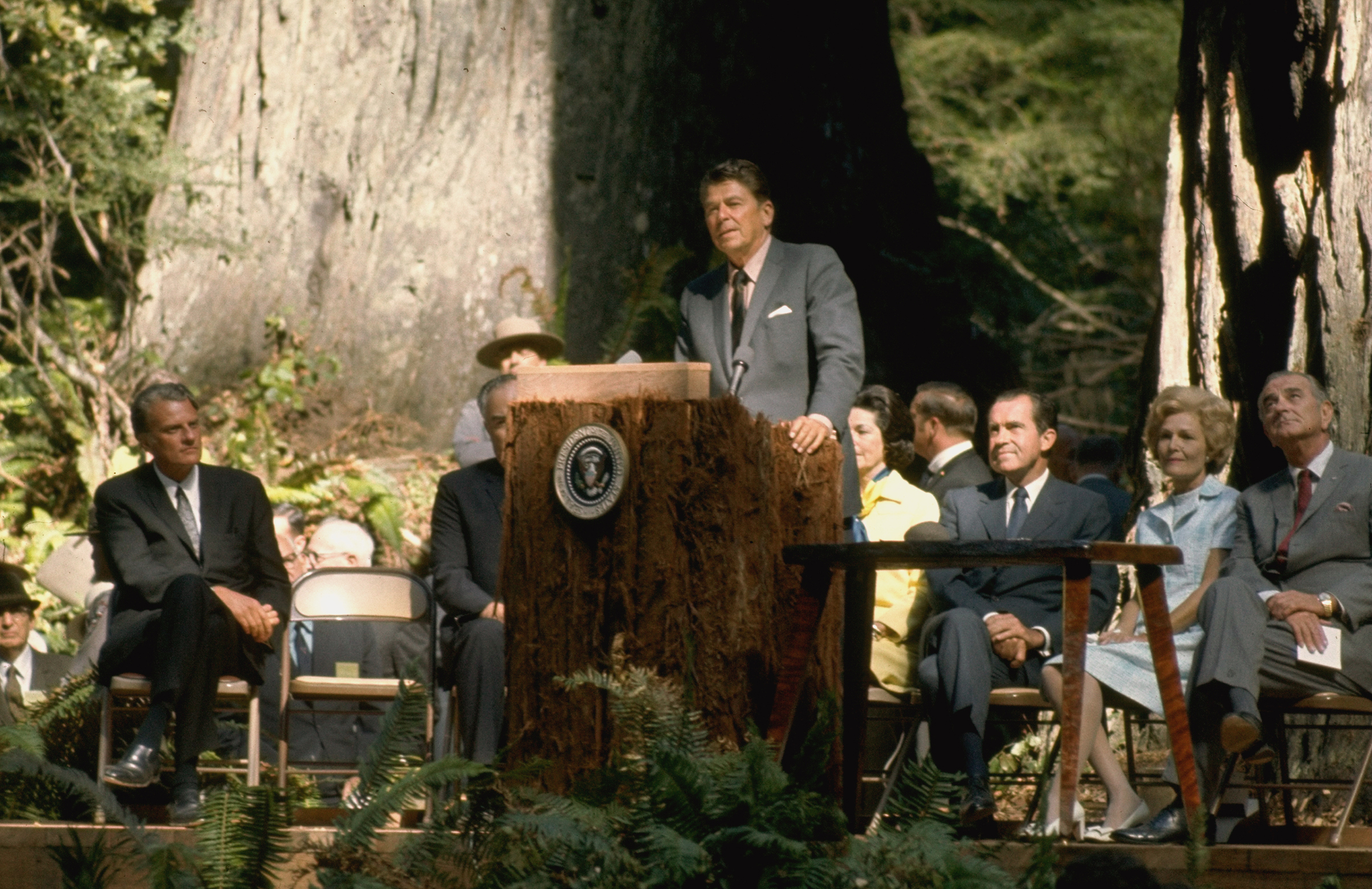 California Governor Ronald Reagan speaking while standing at podium as Reverend Billy Graham, Richard Nixon and wife Pat and Lyndon Johnson look on at Redwood National Park.