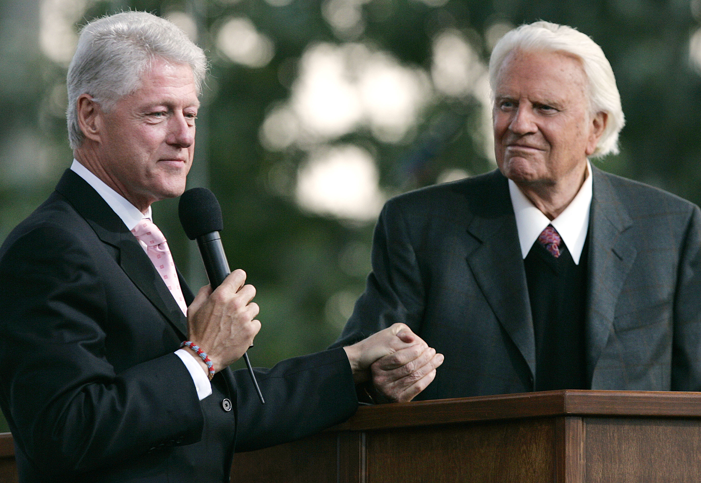 Former U.S. President Bill Clinton holds Billy Graham's hand as he speaks during Graham's Crusade at Flushing Meadows Corona Park on June 25, 2005.