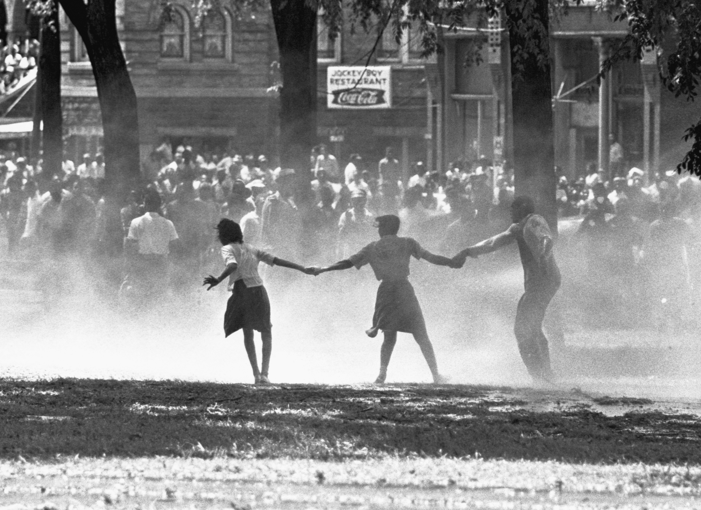 Three demonstrators join hands to build strength against the force of water sprayed by riot police in Birmingham, Alabama, during a protest of segregation practices in May of 1963.