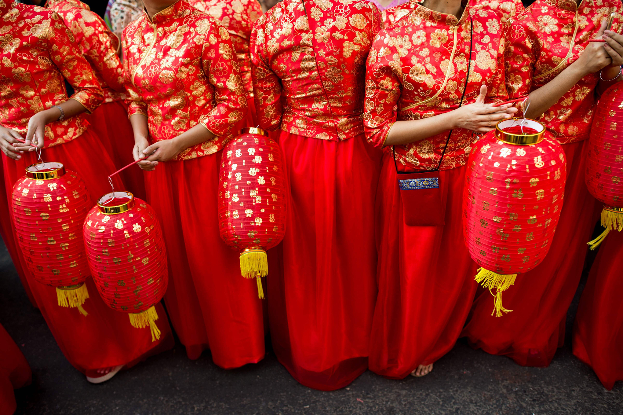 Young women in traditional Chinese costumes hold lanterns as they take part in celebrations marking the first day of the Lunar New Year in Yangon's Chinatown district on Feb. 16, 2018.
