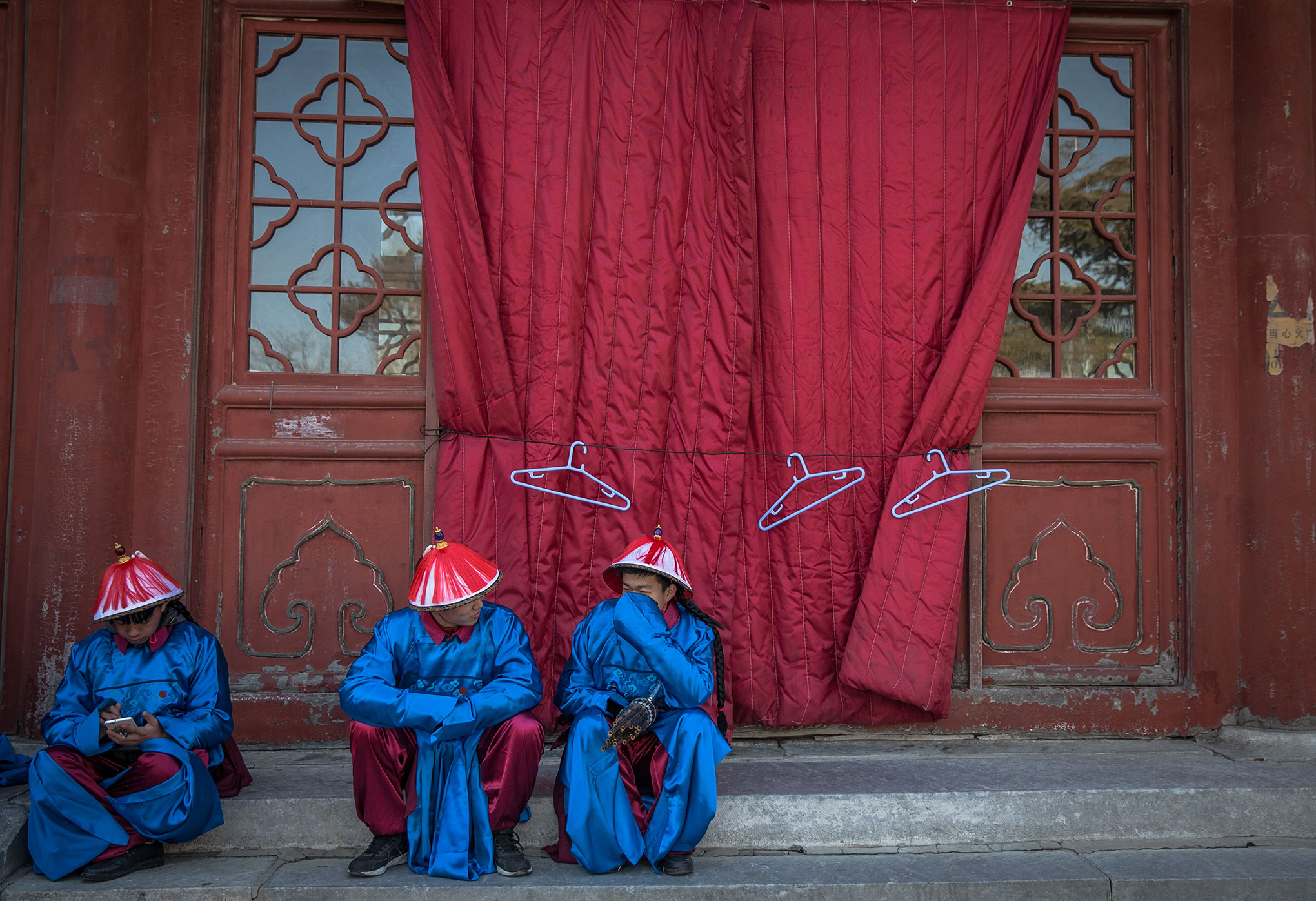 Chinese performers dressed in traditional costumes rest as they attend a rehearsal of a reenactment of a Qing Dynasty imperial sacrifice ritual to worship the Earth, on the eve of the Chinese Lunar New Year, at Ditan Park in Beijing, Feb. 15, 2018.