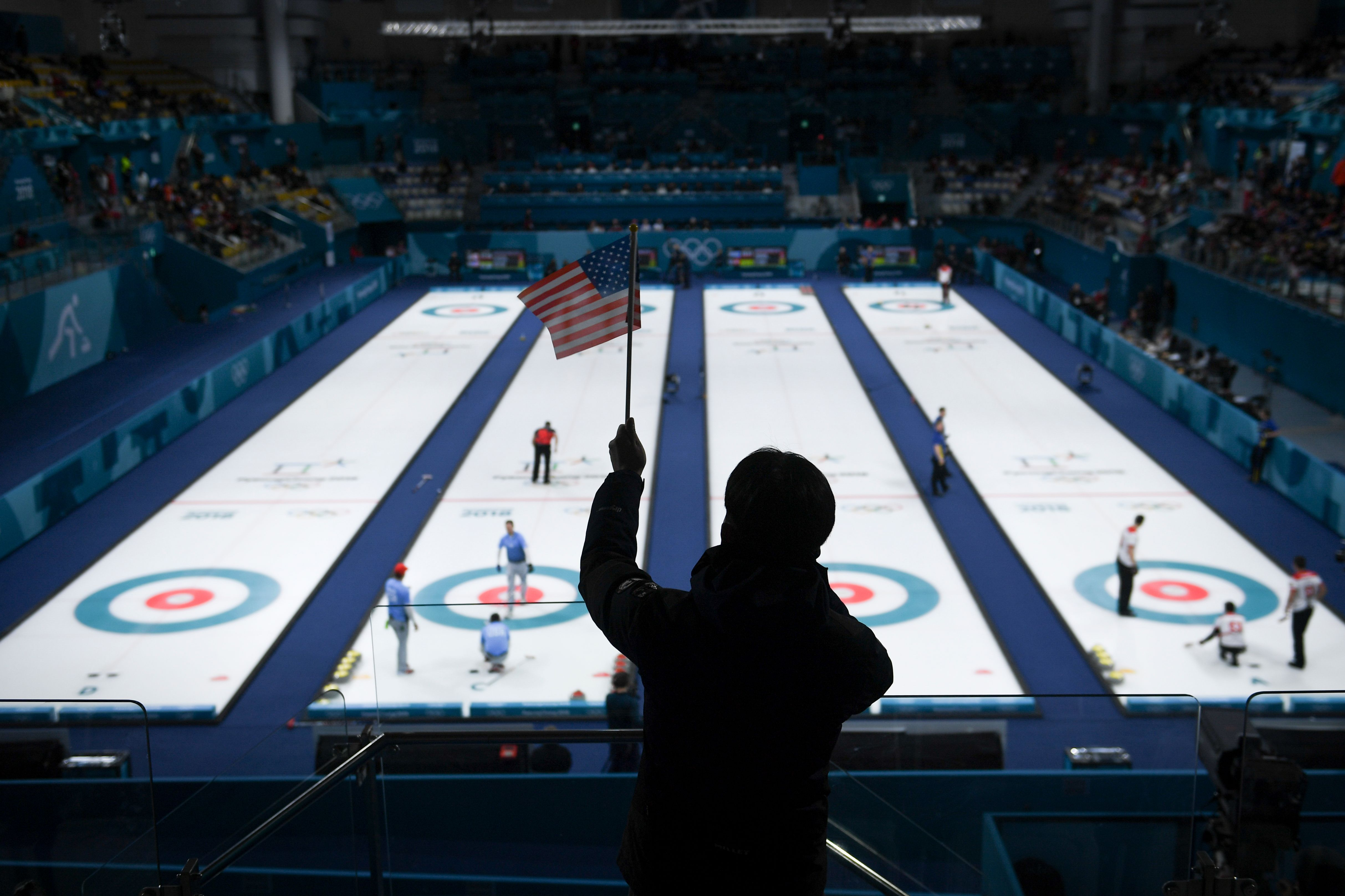 A man waves an American flag during the curling men's semi-final game between Canada and USA during the Pyeongchang 2018 Winter Olympic Games at the Gangneung Curling Centre in Gangneung on February 22, 2018.