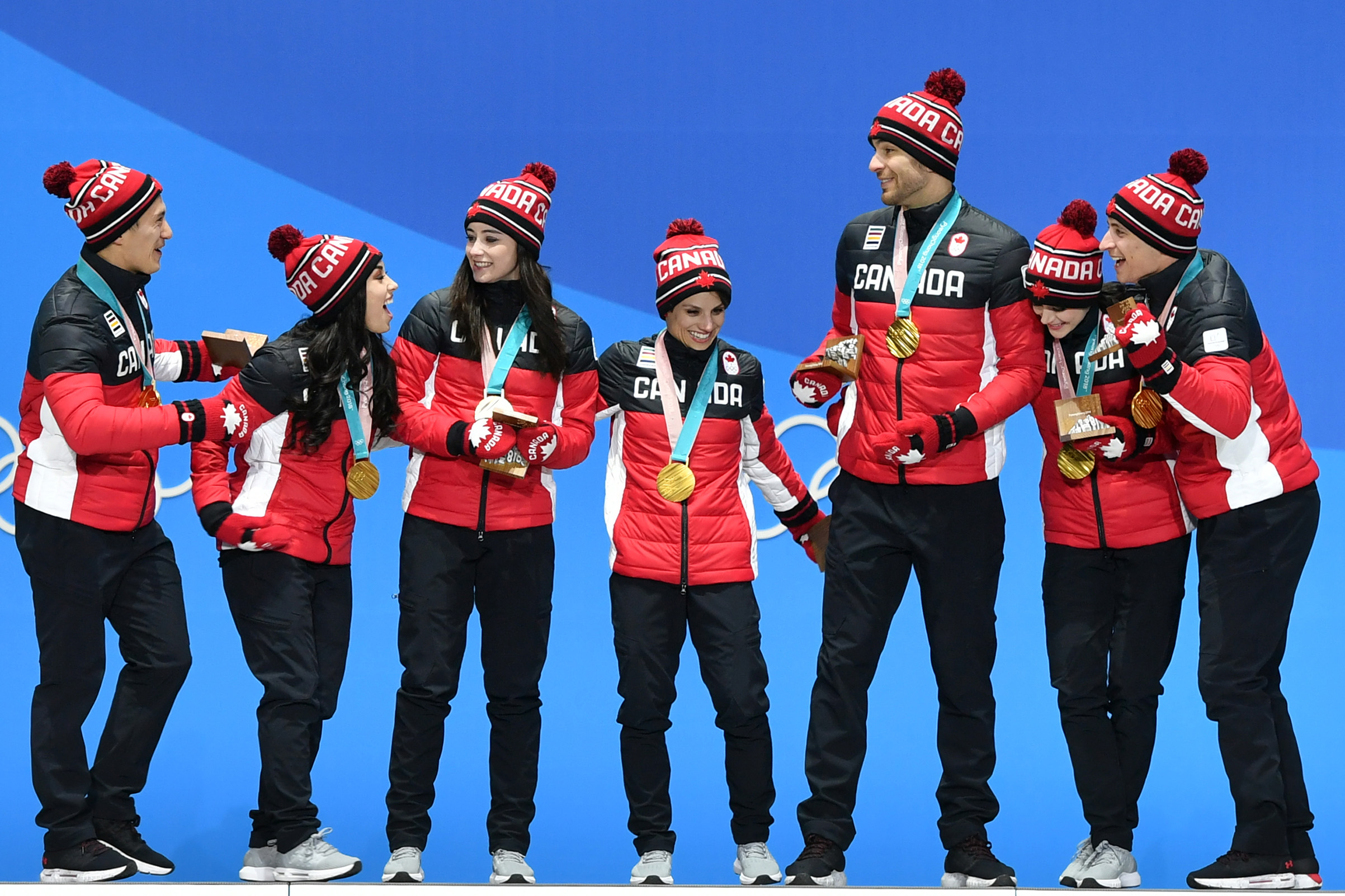 Canada's gold medal-winning team celebrate on the podium during the medal ceremony for the figure skating team event on Feb. 12, 2018.