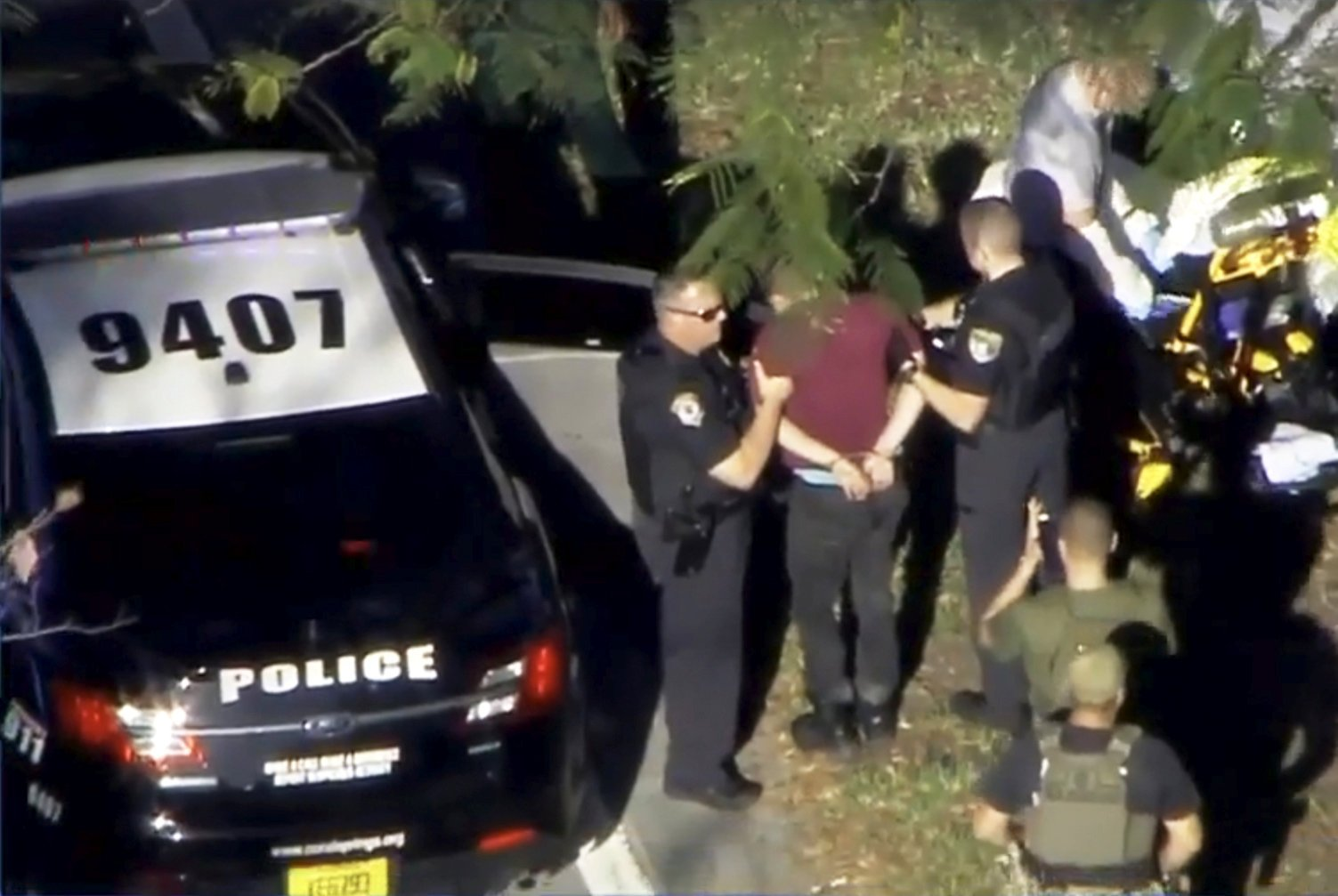 A man placed in handcuffs is led by police near Marjory Stoneman Douglas High School following a shooting incident in Parkland, Fla. Feb. 14, 2018 in a still image from video.