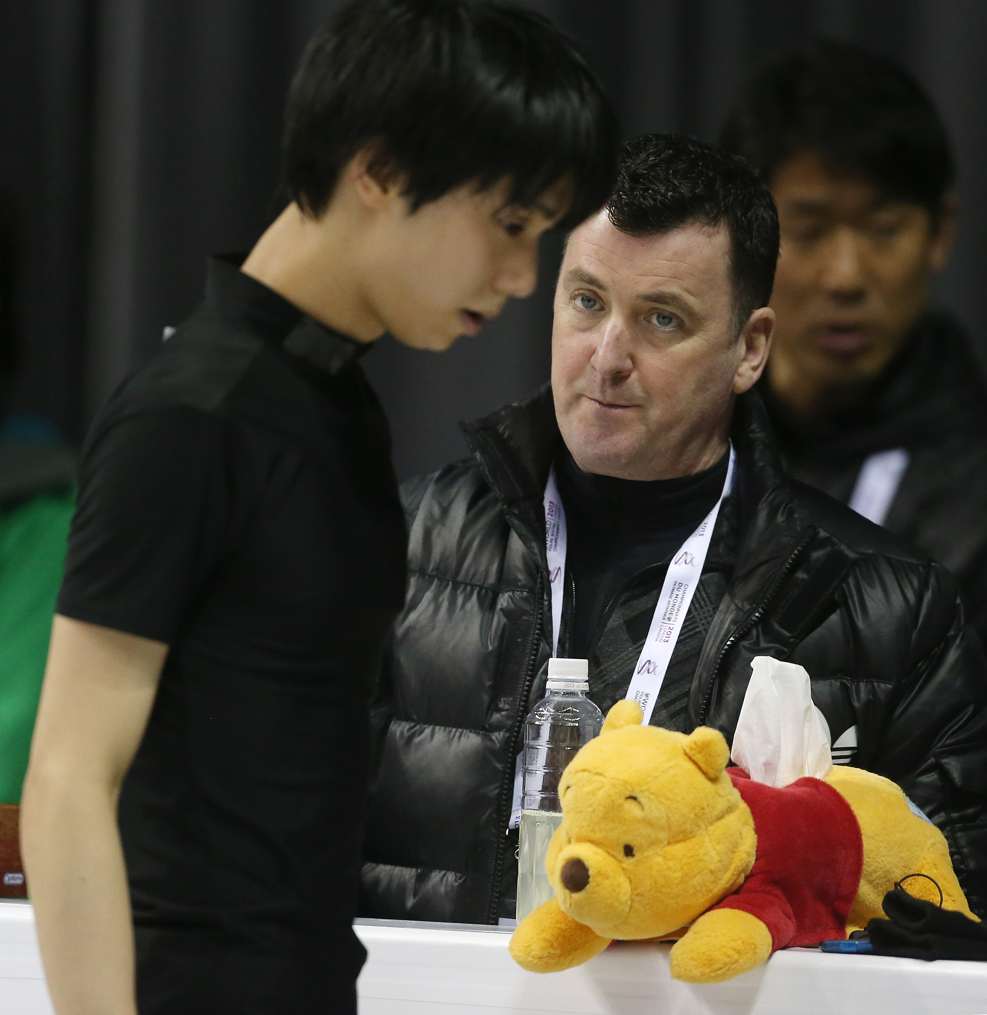 Brian Orser and Winnie the Pooh look on as their skater, Japan's Yuzuru Hanyu practices in preparation for the ISU World Figure Skating Championships at Budweiser Gardens.