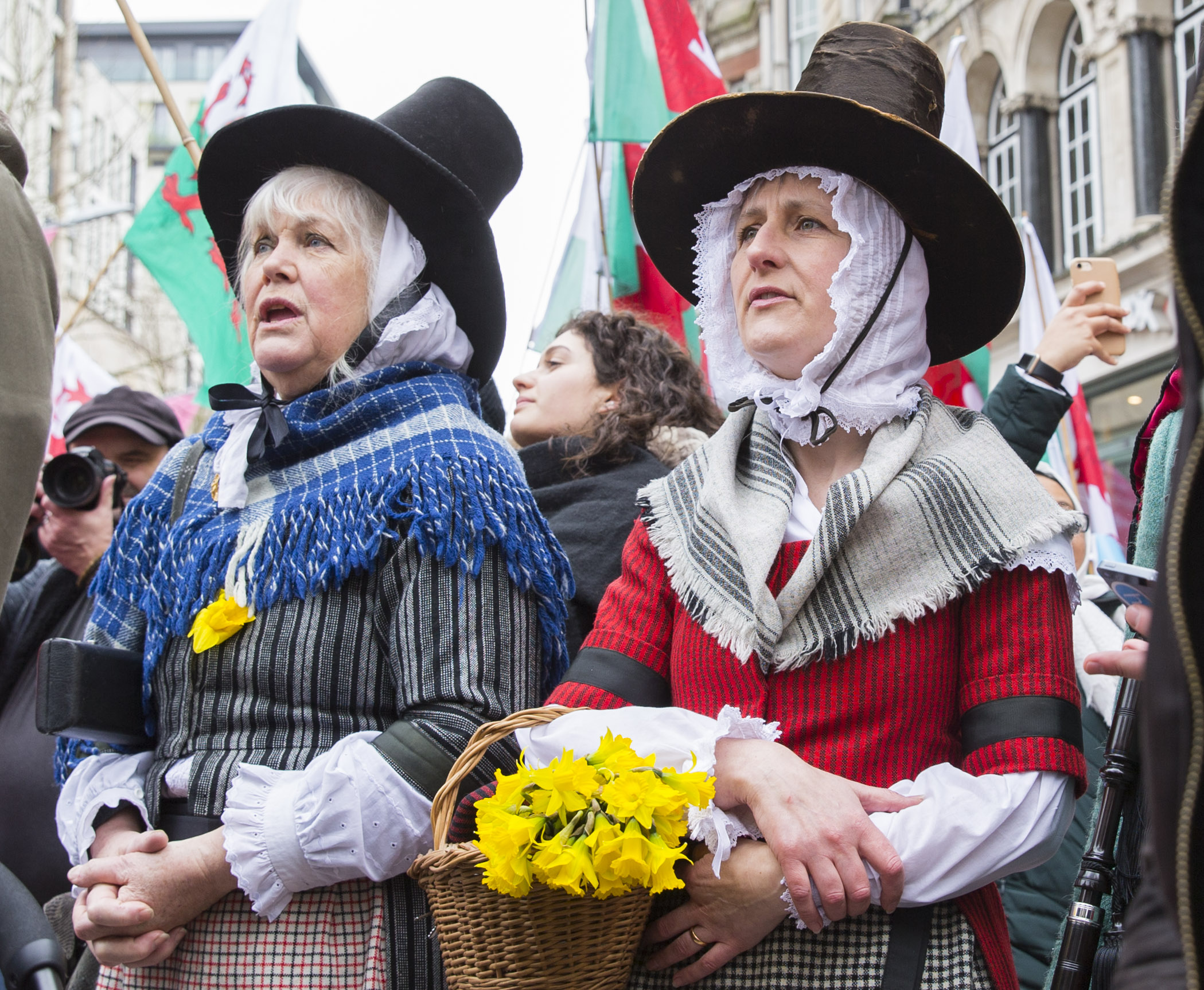 Women in traditional Welsh dress sing the Welsh national anthem during St David's Day parade on March 1, 2017 in Cardiff, Wales.