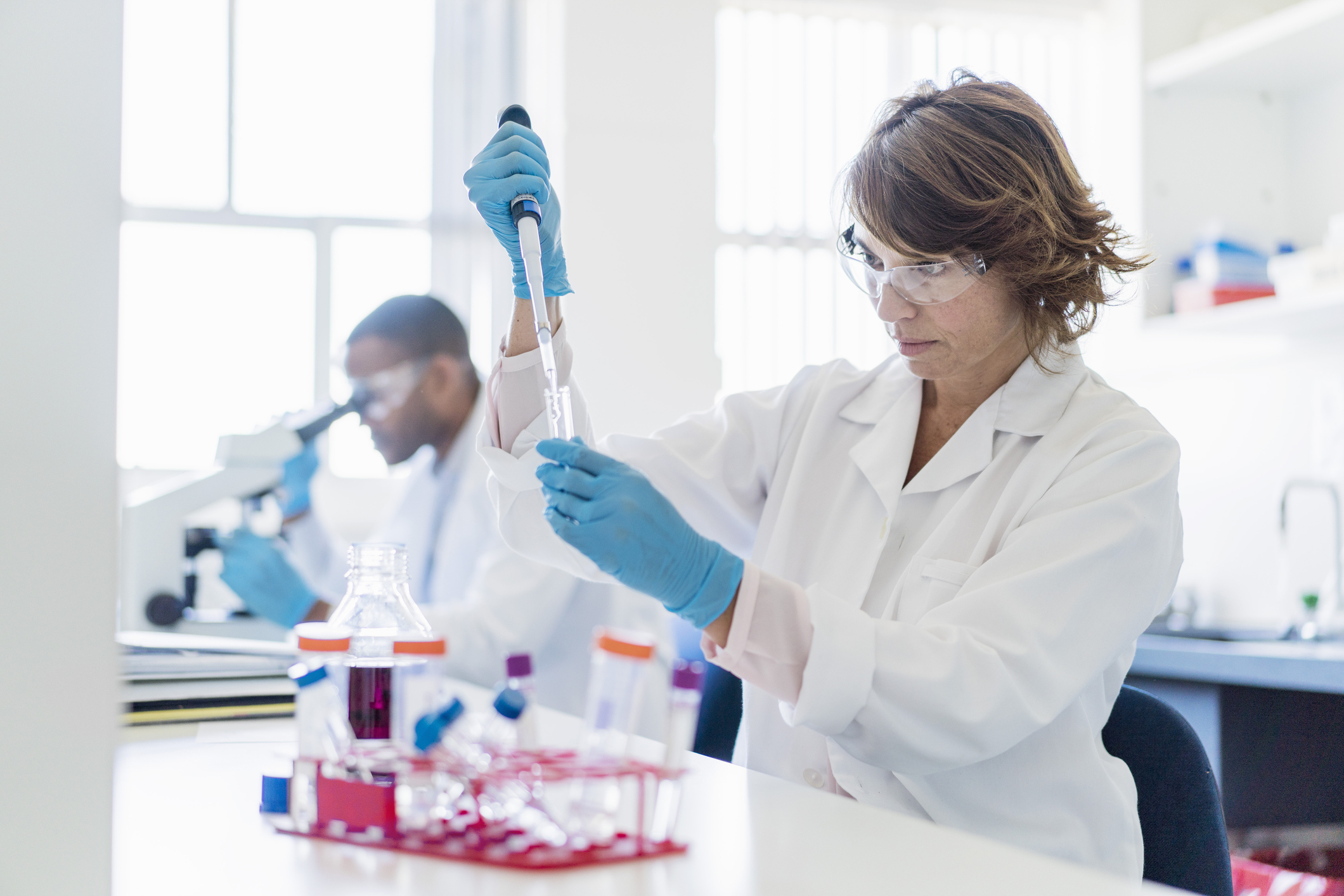 A photo of concentrated chemist working on chemicals. Female scientist using pipette with colleague in background. They are in laboratory.