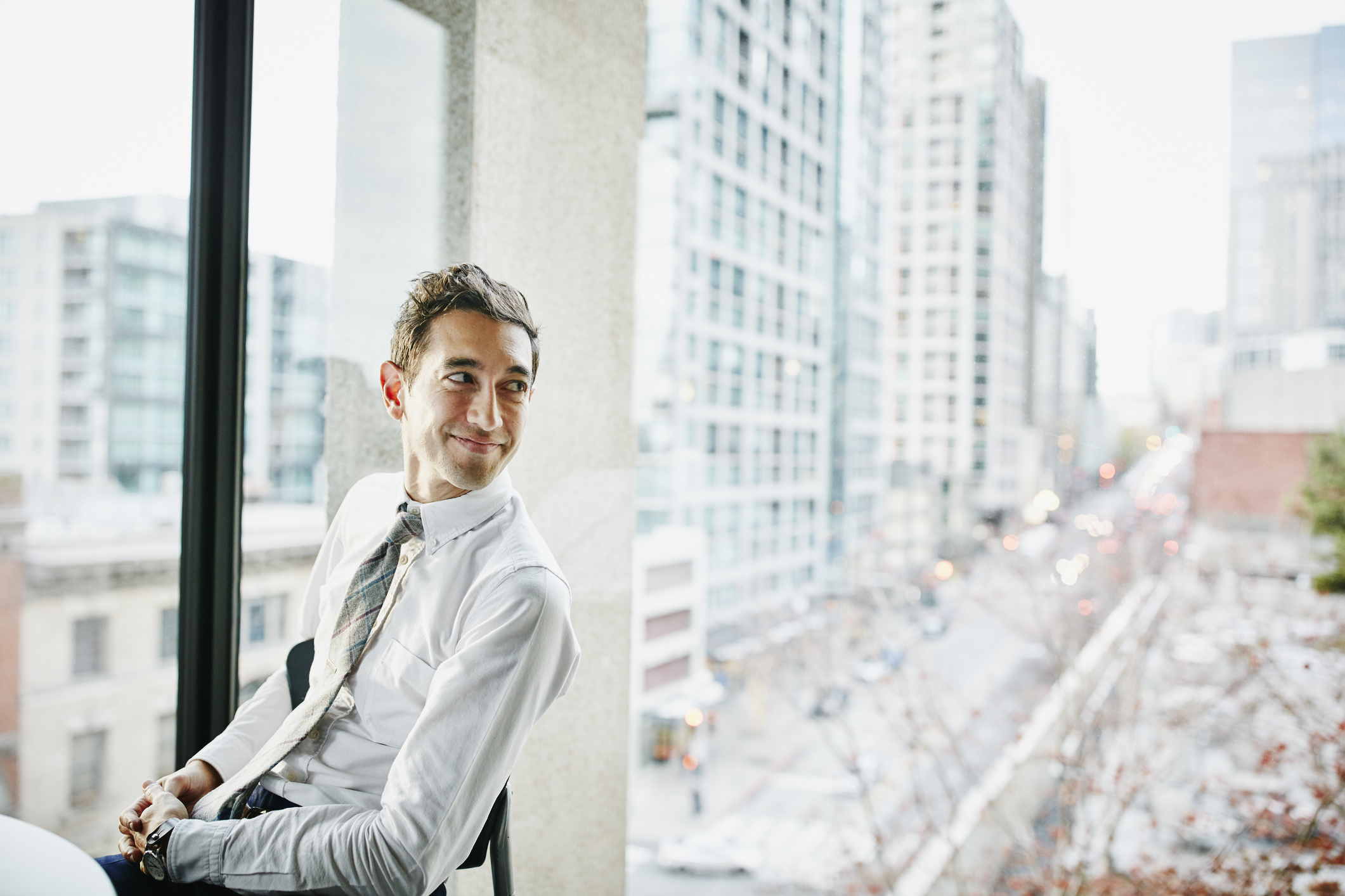 Smiling businessman seated in office with view of city