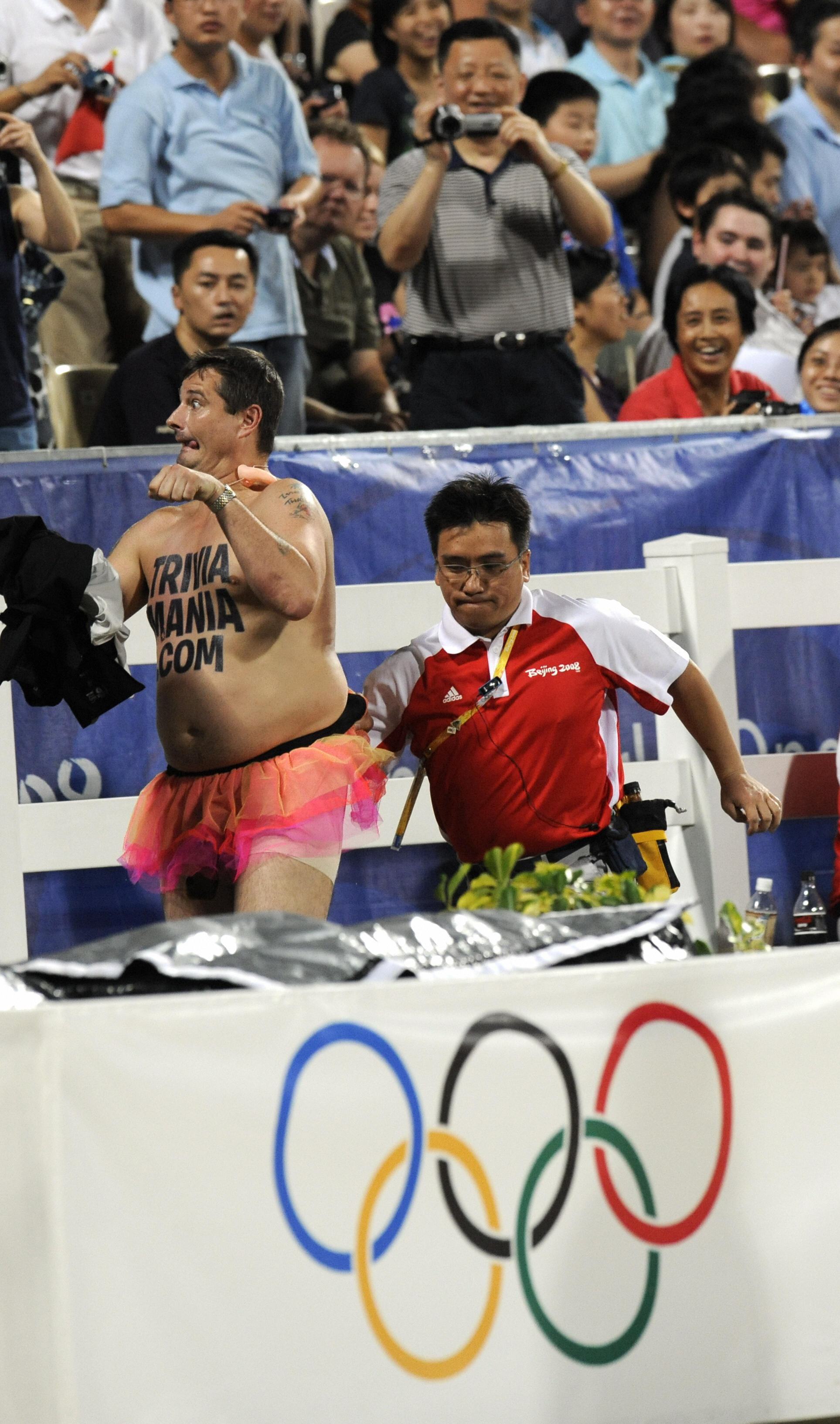 An Official escorts British streaker Mark Roberts after he  performed  during the jumping individual final of the 2008 Beijing Olympic Games on August 21, 2008 in Hong Kong . Ten riders jumped clear rounds in the first of two qualifying rounds of the Olympic individual show jumping final here Thursday. AFP PHOTO/DDP/DAVID HECKER (Photo credit should read DAVID HECKER/AFP/Getty Images)