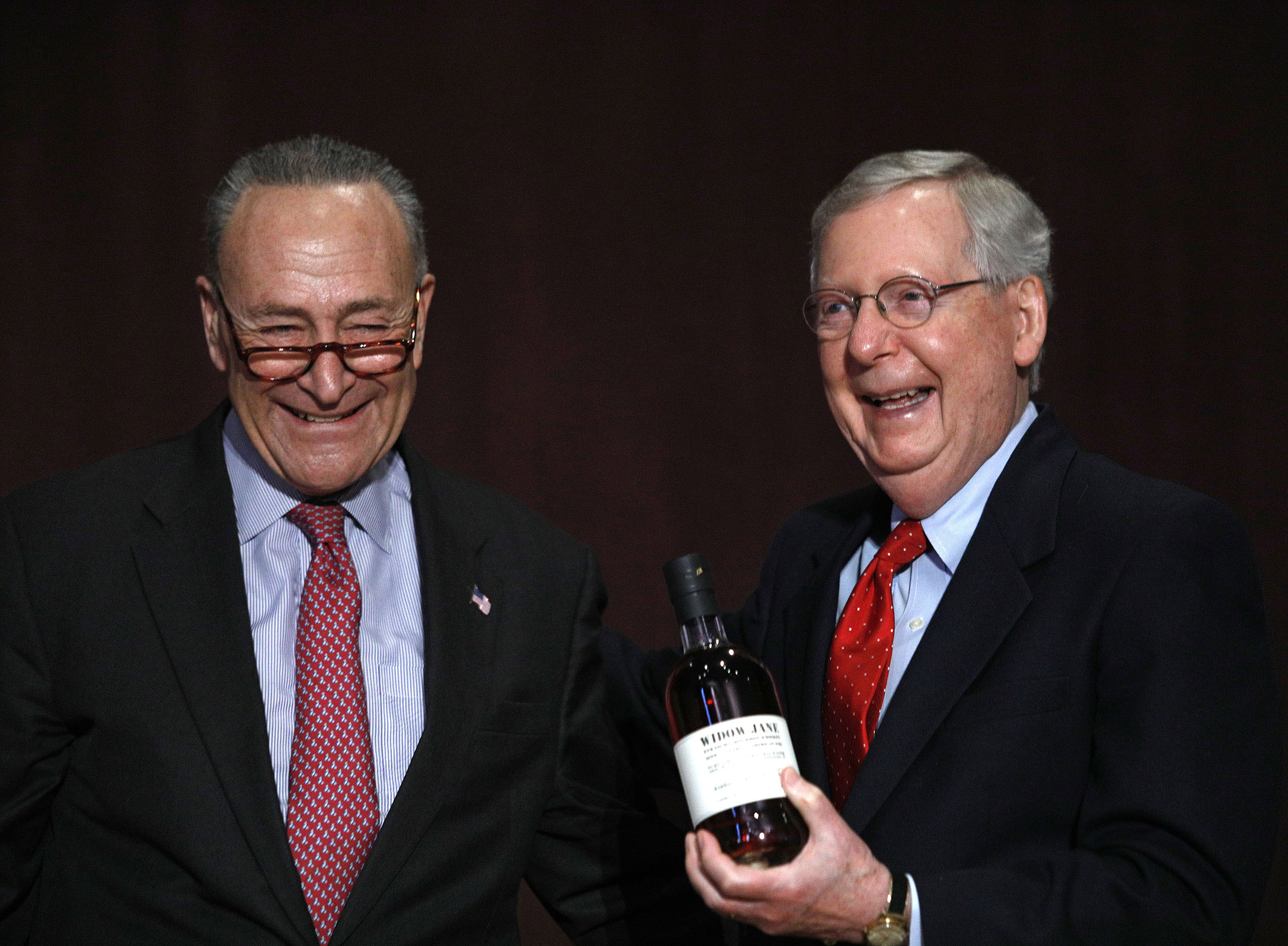 U.S. Senate Democratic Leader Chuck Schumer  (left) (D-NY), presents U.S. Senate Majority Leader Mitch McConnell (right) (R-KY) with a bottle of bourbon at the University of Louisville's McConnell Center where Schumer was scheduled to speak February 12, 2018 in Louisville, Kentucky.
