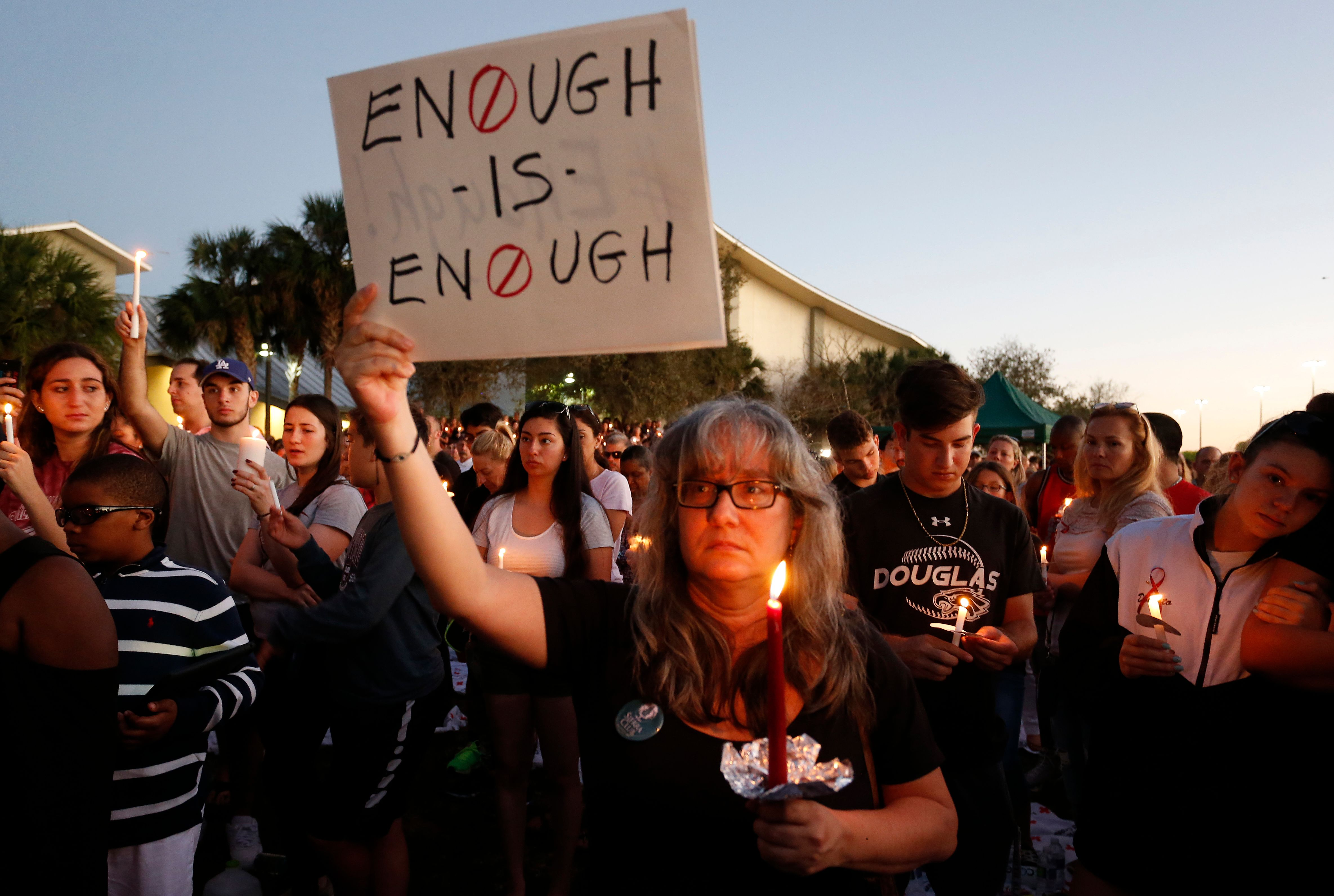 Mourners stand during a candlelight vigil for the victims of Marjory Stoneman Douglas High School shooting in Parkland, Florida on Feb. 15, 2018.