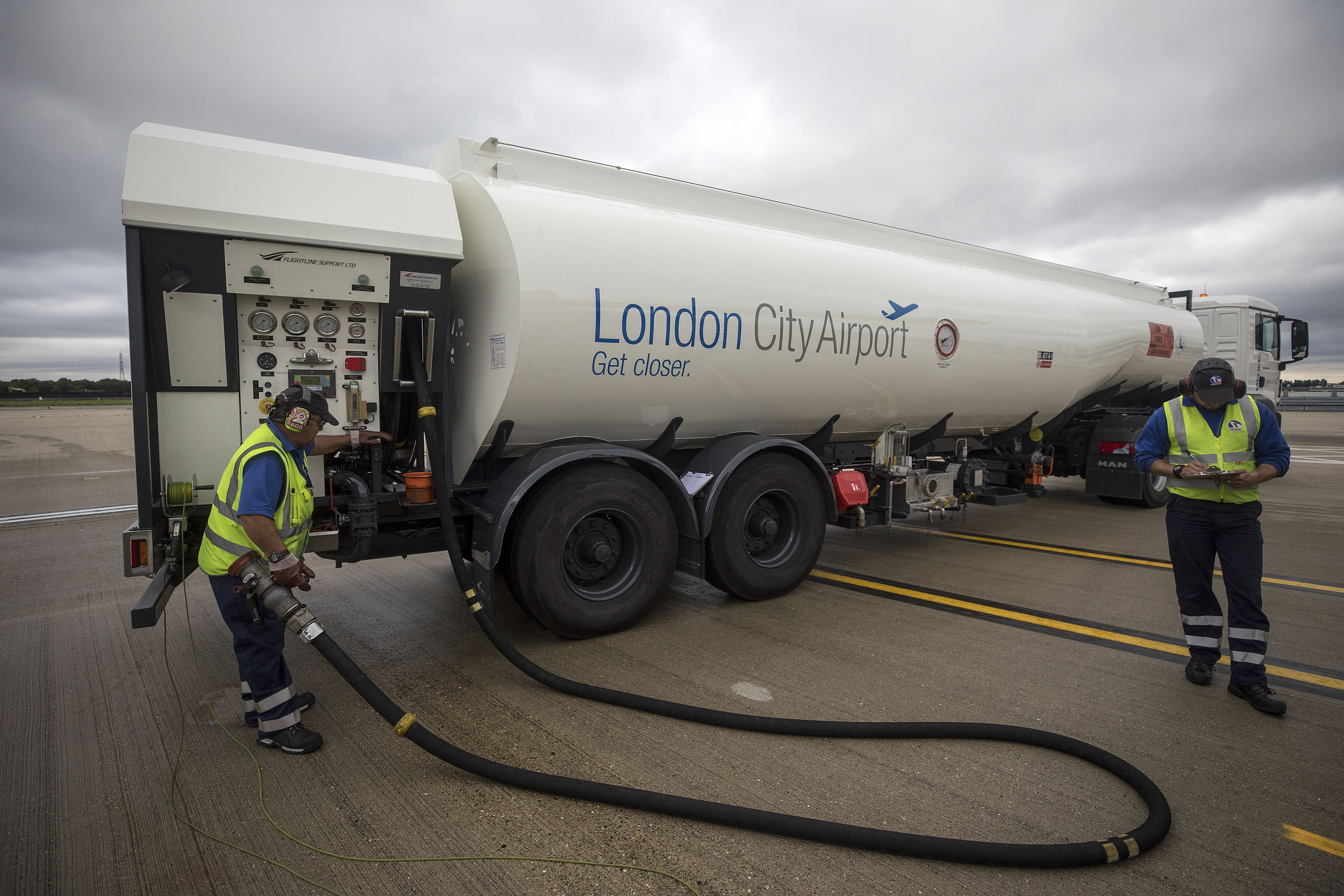 Members of the ground crew move a fuel hose at London City Airport (LCY), in London, U.K., on Tuesday, Aug. 8, 2017. The chief Brexit concern of carriers is to maintain a single market for air travel which wouldallow existing routes between Britain and the EU to continue.