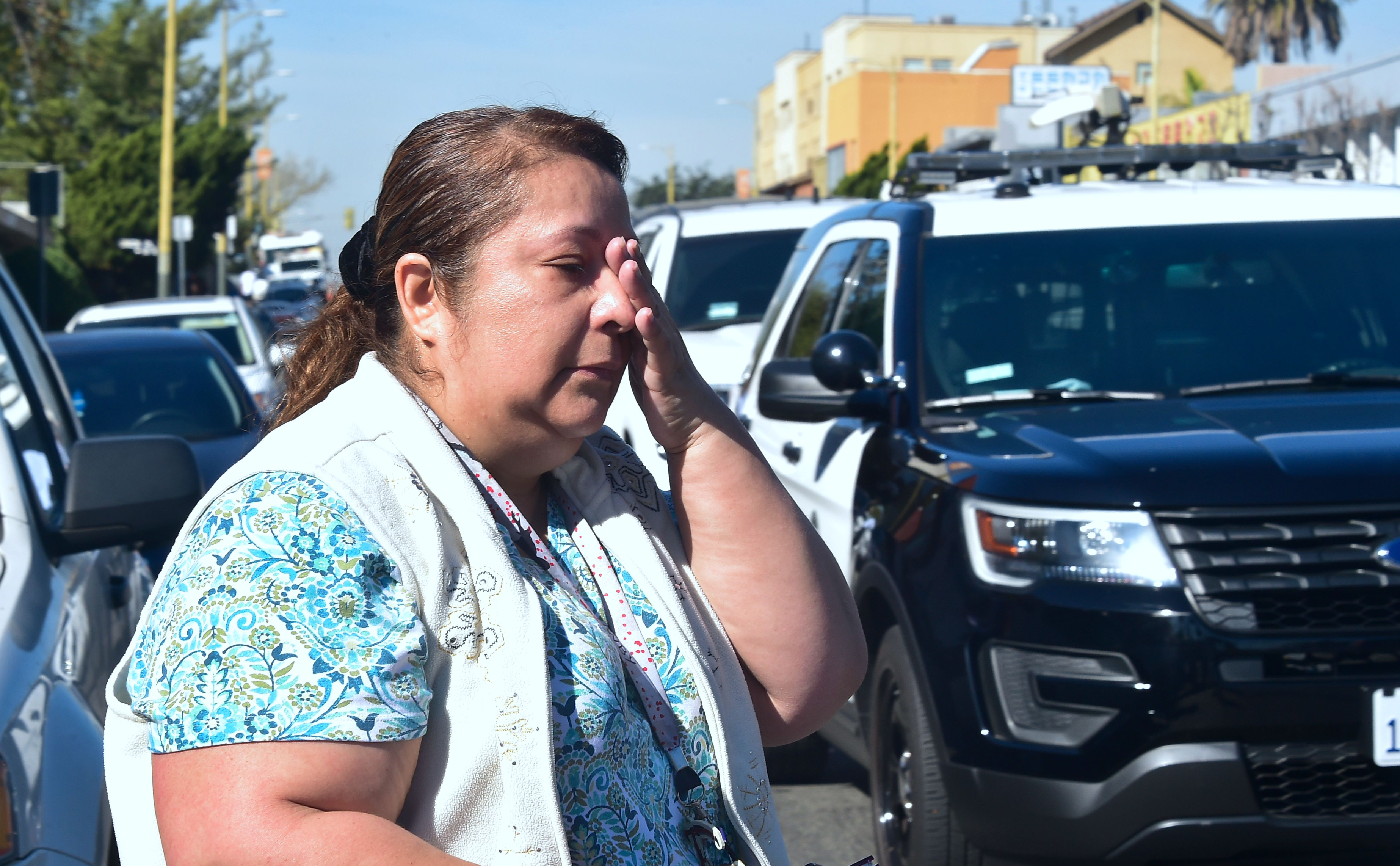 A parent reacts while crossing the street past police vehicles outside a roadblock near Salvadore Castro Middle School in Los Angeles, California on February 1, 2018, where two students were wounded, one critically, in a school shooting.                      Two 15-year-old students in Los Angeles were shot and wounded in class Thursday, according to witnesses and local media, in the latest school shooting to hit the United States. A boy was shot in the head, while a girl was hit in the wrist, according to reports from the scene. Local news agency CNS reported that a  young woman,  possibly a fellow student, had been arrested.                       / AFP PHOTO / Frederic J. Brown        (Photo credit should read FREDERIC J. BROWN/AFP/Getty Images)