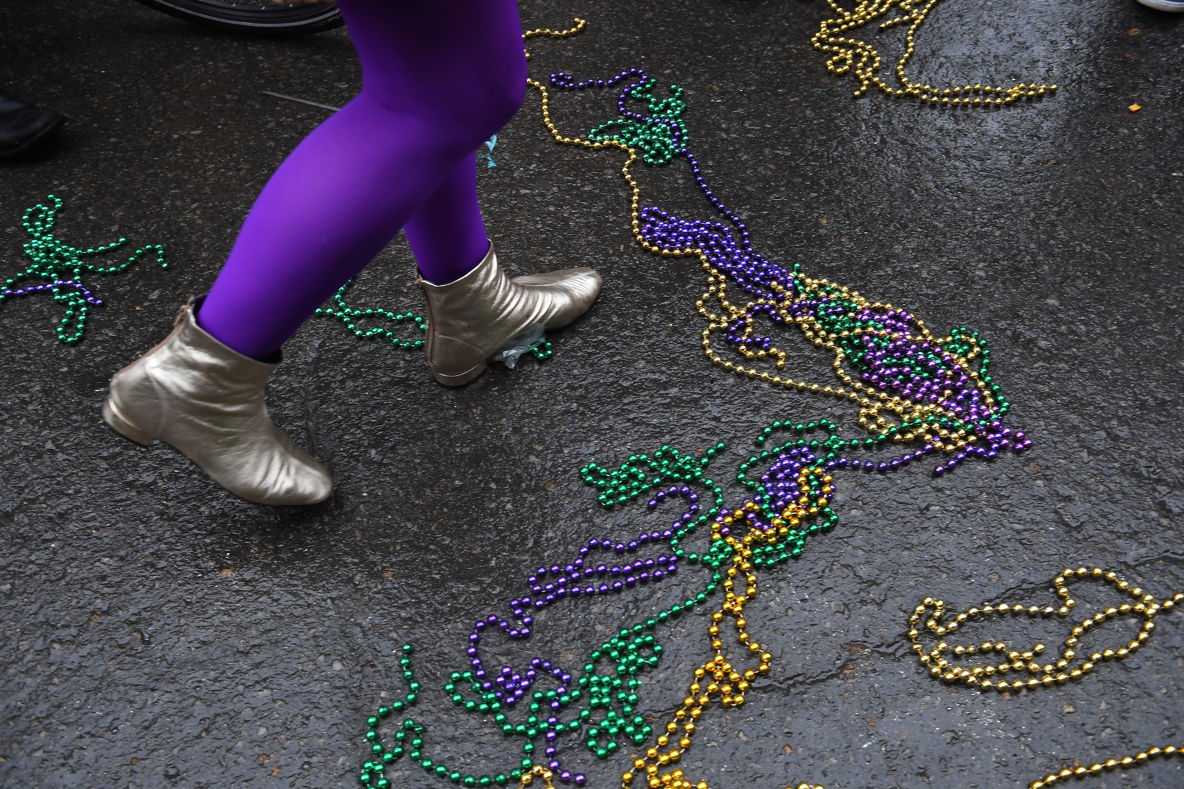 A person walks among beads during a parade on Feb. 17, 2017, in New Orleans.