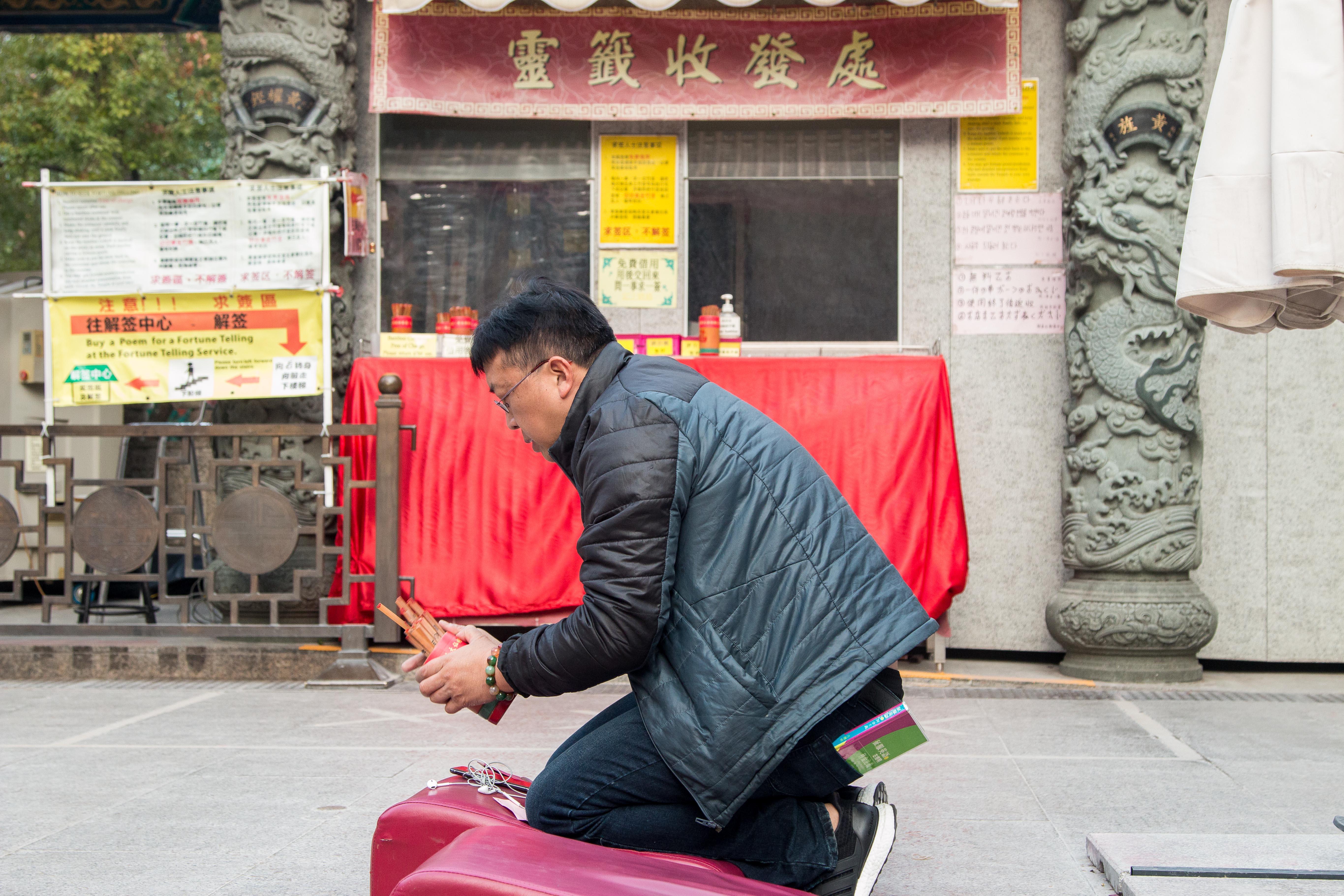A temple visitor demonstrates excellent kau cim technique.