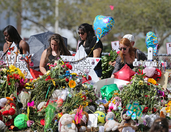 Mourners bring flowers to pay tribute at a memorial for the victims of the shooting at Marjory Stoneman Douglas High School on Sunday, February 25, 2018.