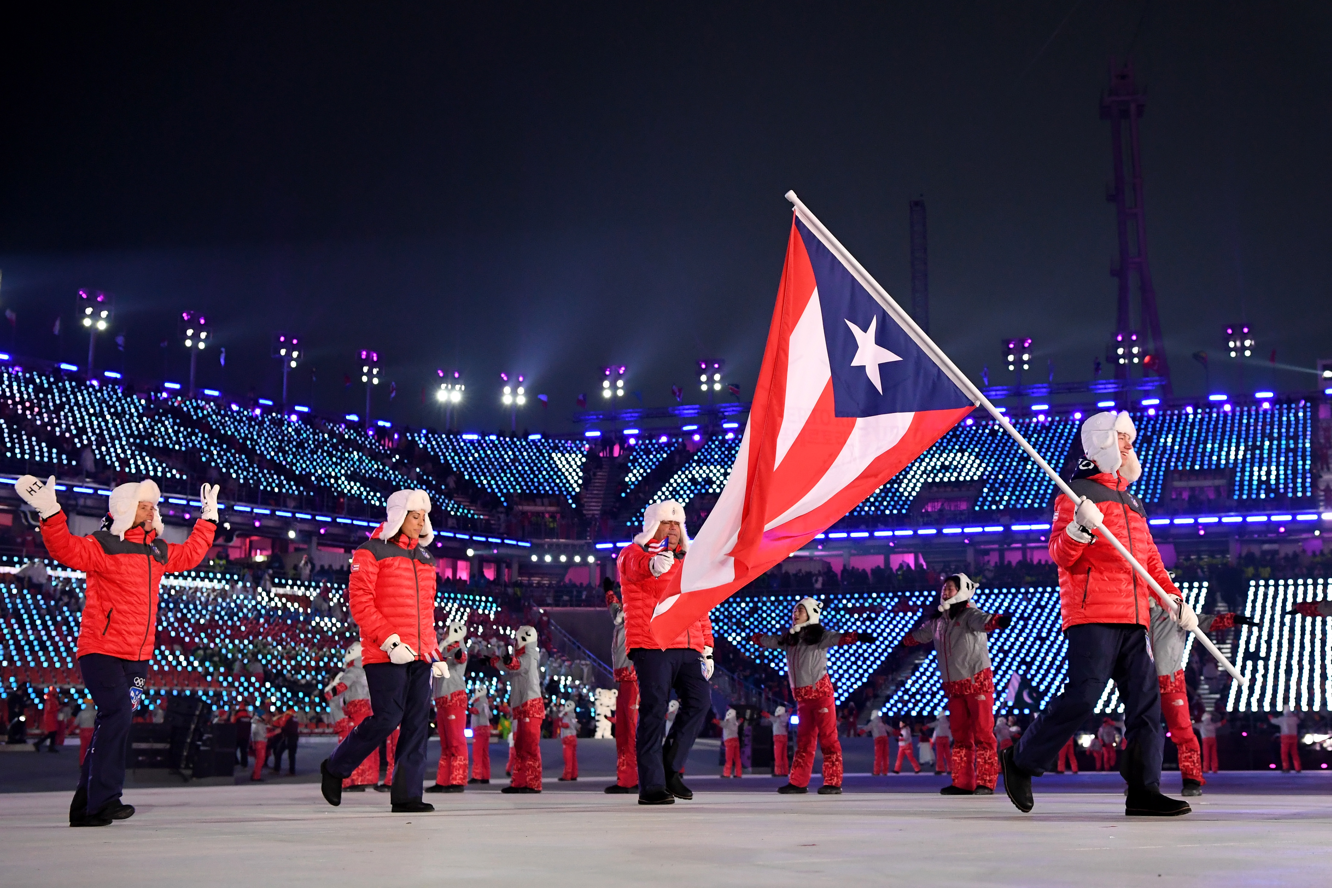 Flag bearer Charles Flaherty of Puerto Rico and teammates arrive at the stadium during the Opening Ceremony of the PyeongChang 2018 Winter Olympic Games at PyeongChang Olympic Stadium on February 9, 2018 in Pyeongchang-gun, South Korea.