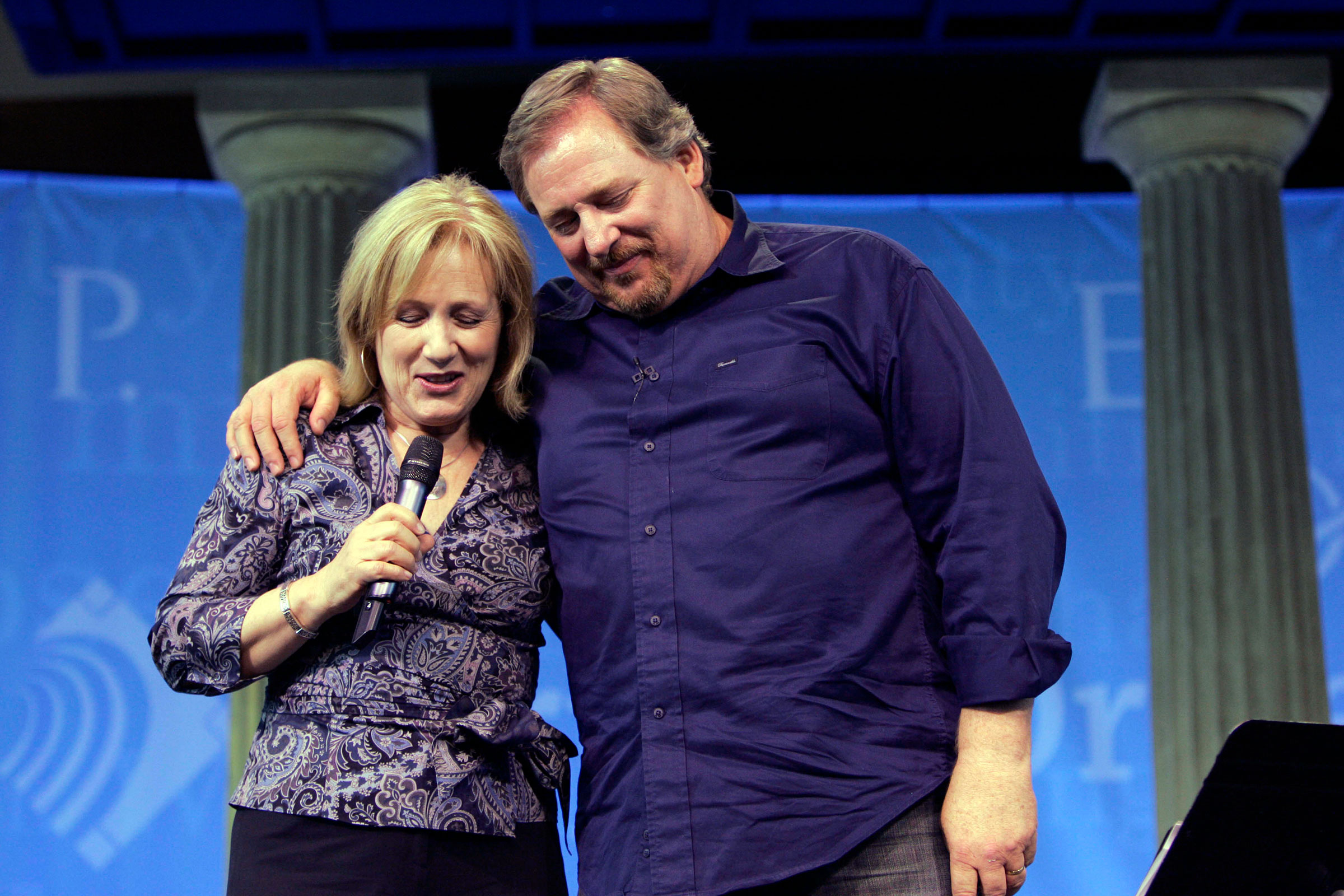 Kay Warren, left, is joined by her husband Pastor Rick Warren, as she leads a prayer at Saddleback Church in Lake Forest, May 20, 2008.