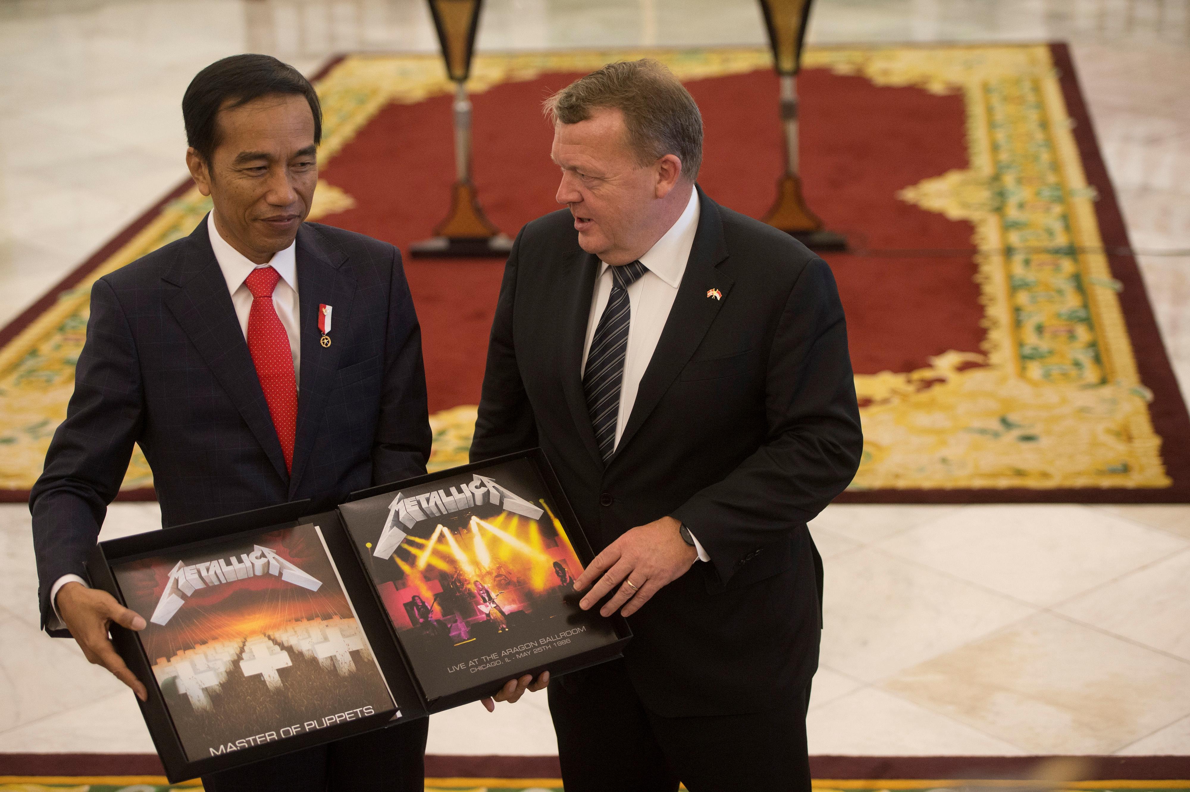 Indonesian President Joko Widodo receives a Metallica vinyl record from Denmark's Prime Minister Lars Lokke Rasmussen in Bogor, Indonesia on Nov. 28, 2017.