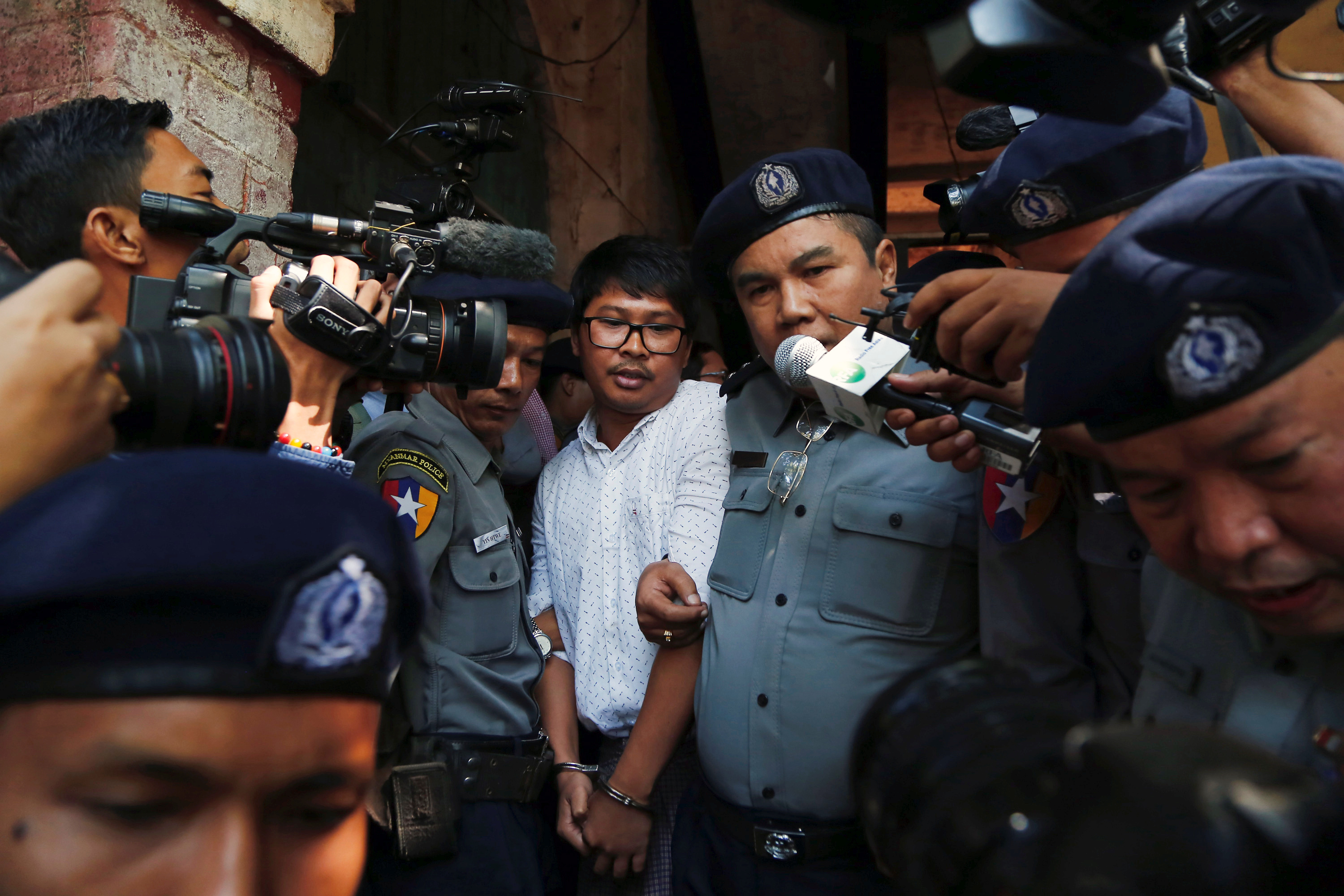 Detained Reuters journalist Wa Lone is escorted by police after a court hearing in Yangon, Myanmar on Feb. 6, 2018.