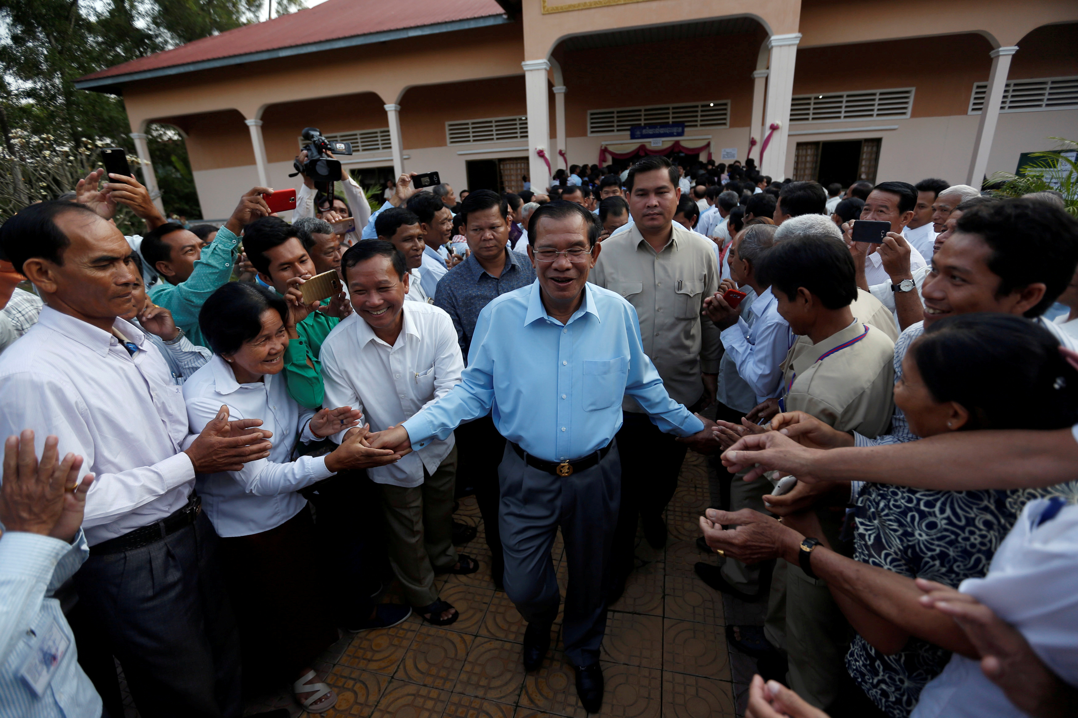 Cambodia's Prime Minister Hun Sen surrounded by commune counselors during at a Senate election polling station in Takhmao, Kandal province, Cambodia on Feb. 25, 2018.