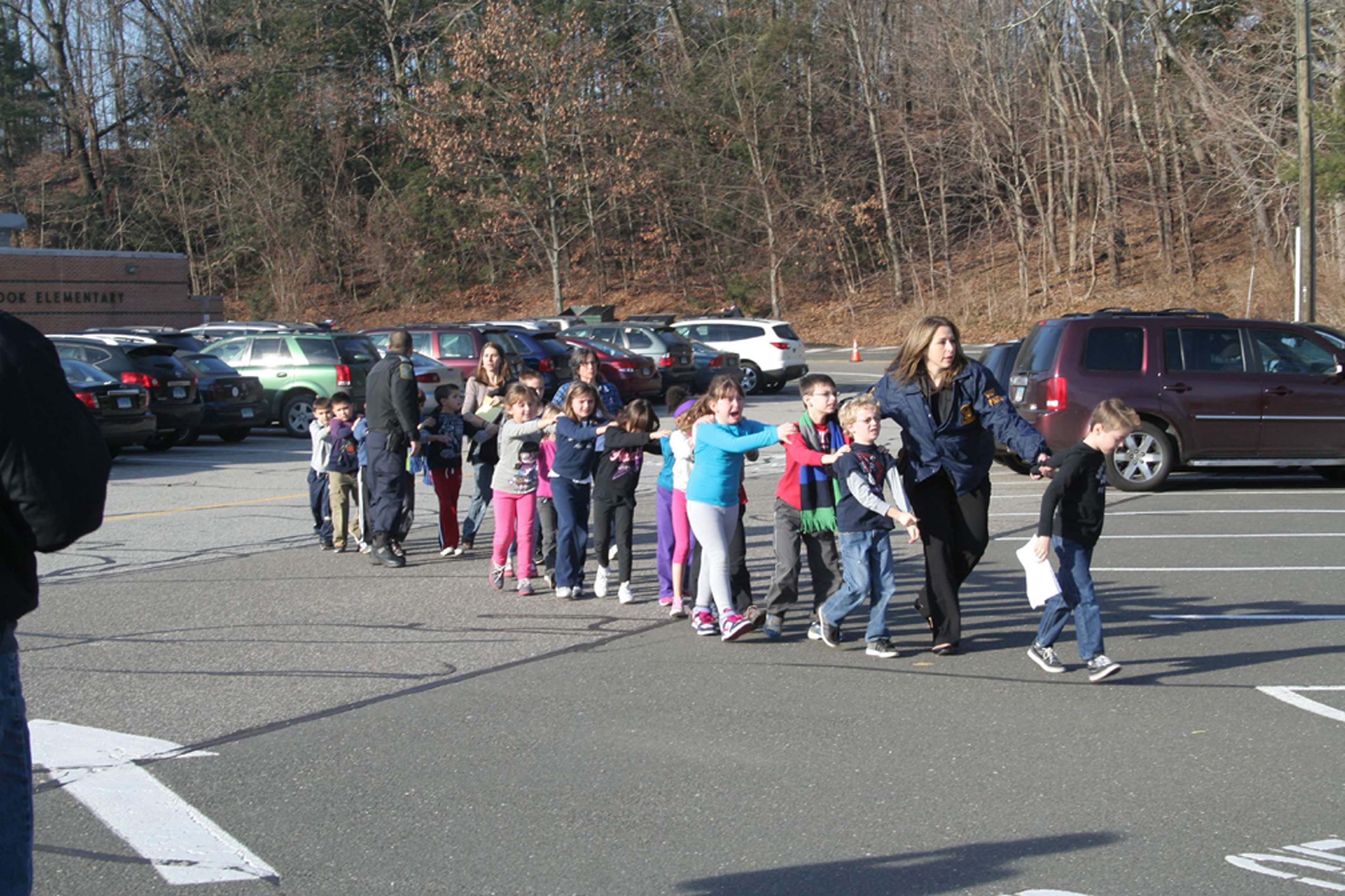 Connecticut State Police lead students from the Sandy Hook Elementary School to safety after a mass shooting on Dec. 14, 2012.