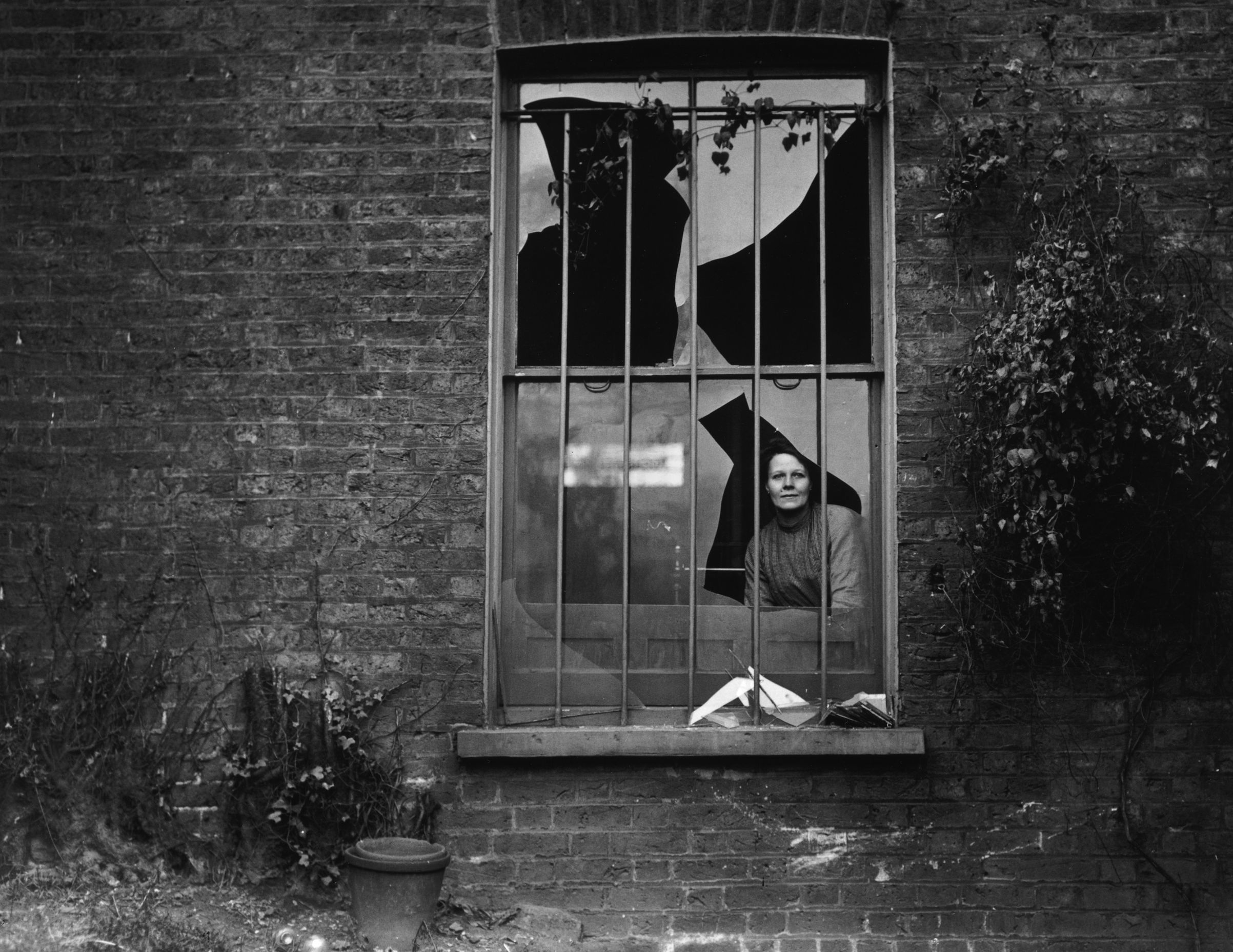 A woman peers through a shattered window the day after a bomb attack by suffragettes on nearby Holloway prison, Dec. 19, 1913. No-one was arrested for the attack, but suspicion fell on the Women's Social and Political Union (WSPU).