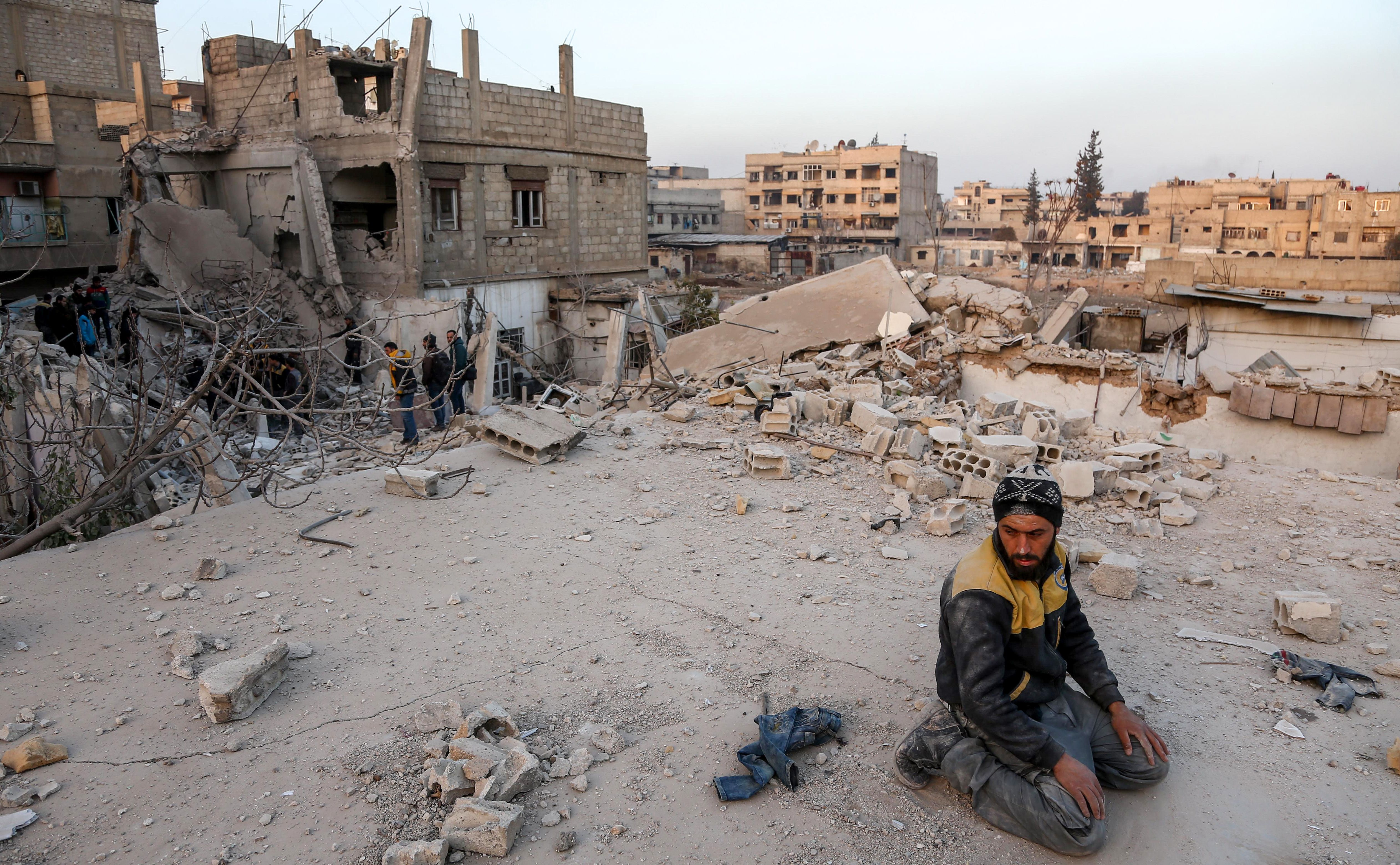 A Syrian civil defense volunteer performs ritual sunset prayers next to the site of a building that collapsed following reported regime air strikes in the rebel-held town of Arbin, in the besieged Eastern Ghouta region on the outskirts of the capital Damascus, on February 6, 2018.