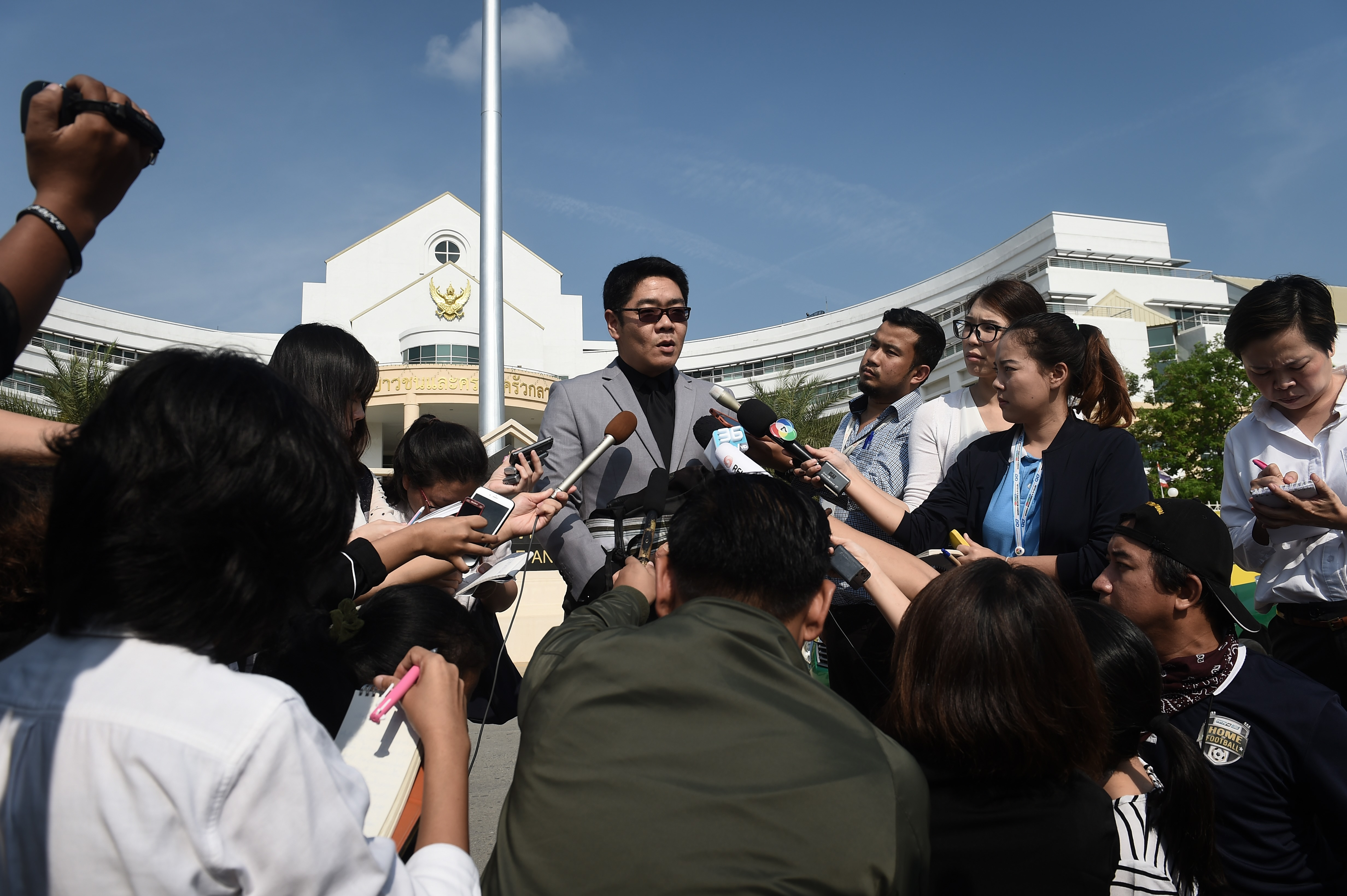 Kong Suriyamontol (C-with sunglasses), the Thai lawyer for Japanese national Mitsutoki Shigeta, speaks to the press after his client was granted paternity rights to his children, at a juvenile court in Bangkok on February 20, 2018.                     A Bangkok court on February 20 granted Shigeta  sole parent  rights to 13 babies fathered through Thai surrogate mothers, a ruling that paves the way for him to take custody of the children.