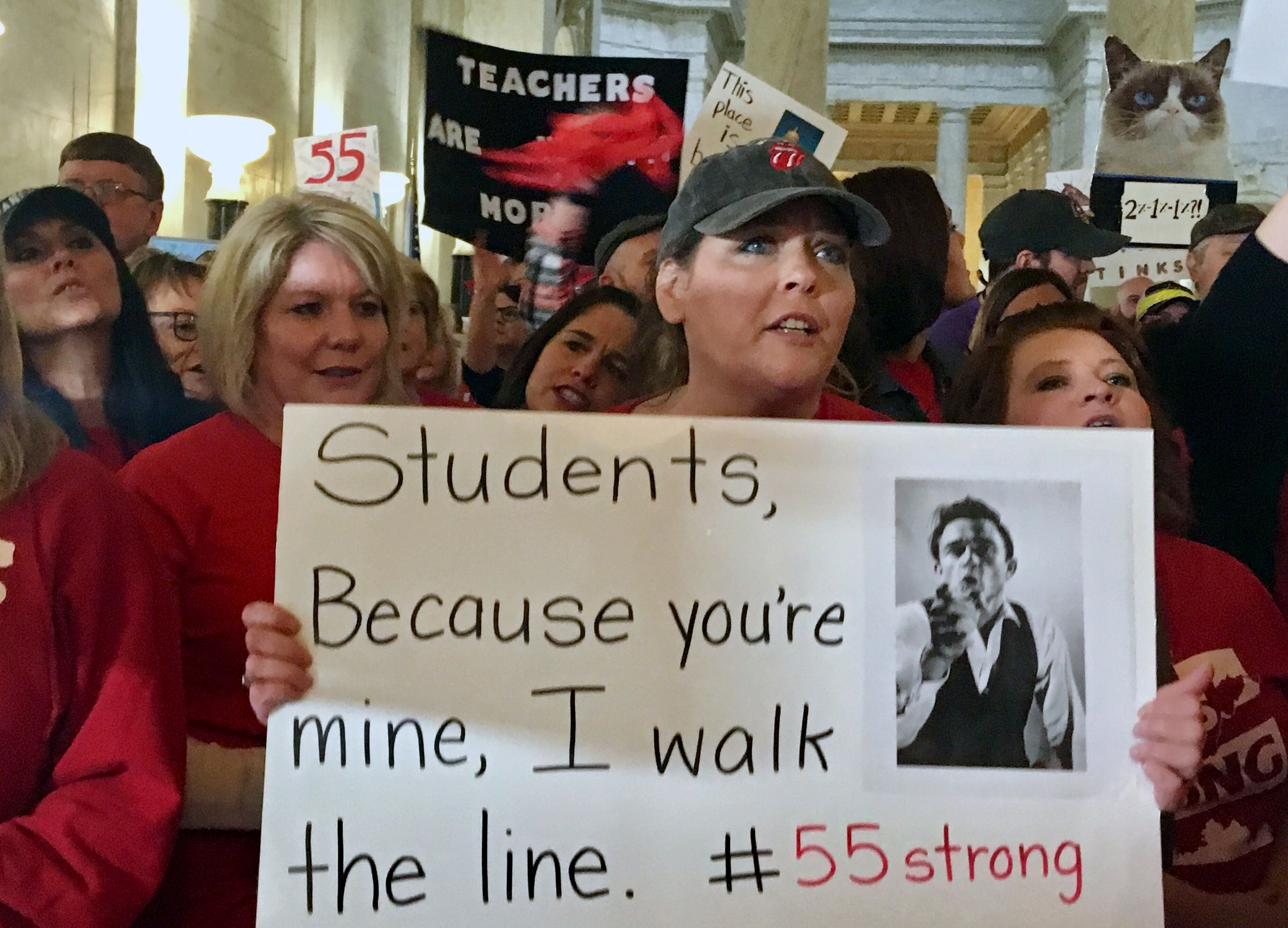 Jennifer Hanner, a first-year teacher from Harts, W.Va., center, holds a sign, outside the state Senate chambers at the Capitol in Charleston, W.Va. Teachers statewide went on strike Thursday over pay and benefits                       Teacher Pay, Charleston, USA - 22 Feb 2018
