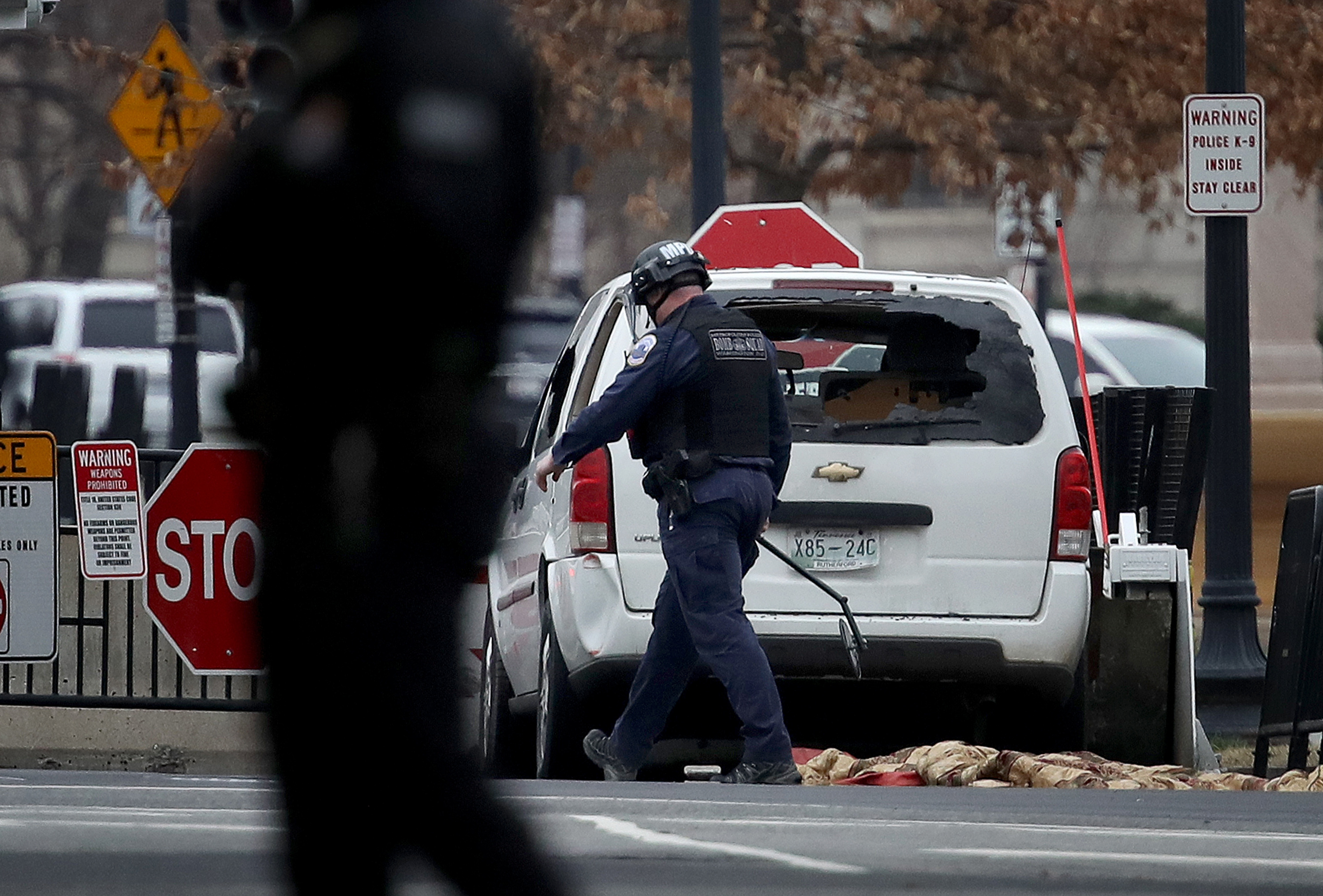 A member of a bomb squad inspects a vehicle that crashed into a barricade on the perimeter of the White House grounds February 23, 2018 in Washington, DC. A female driver was apprehended immediately after the incident by the uniformed division of the United States Secret Service.