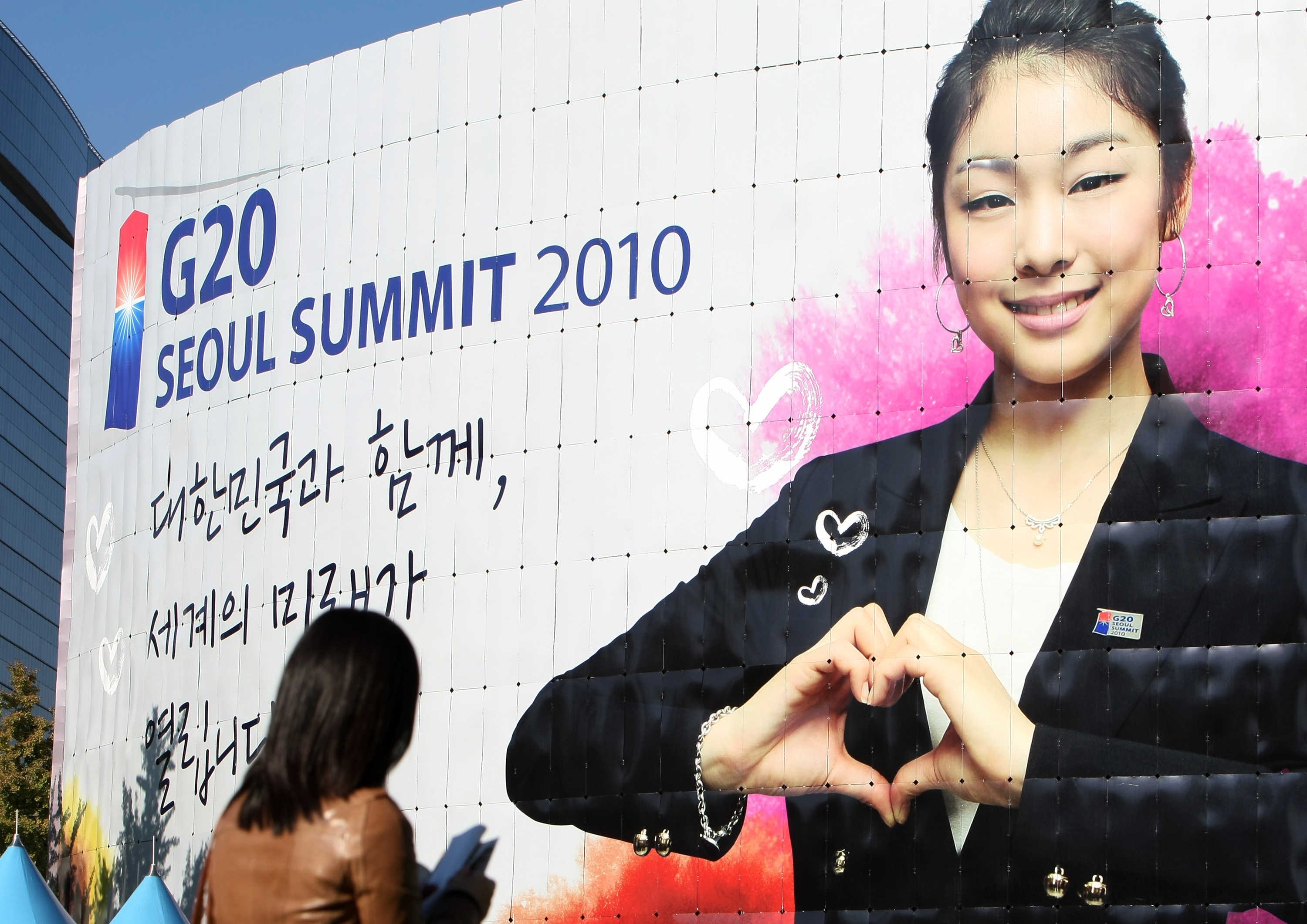 Pedestrians walk past Seoul City Hall, which is covered with a billboard showing a picture of Olympic figure skating gold medalist Kim Yuna, for the Group of 20 (G-20) summit in Seoul, South Korea, on Saturday, Oct. 30, 2010. Photographer: SeongJoon Cho/Bloomberg via Getty Images