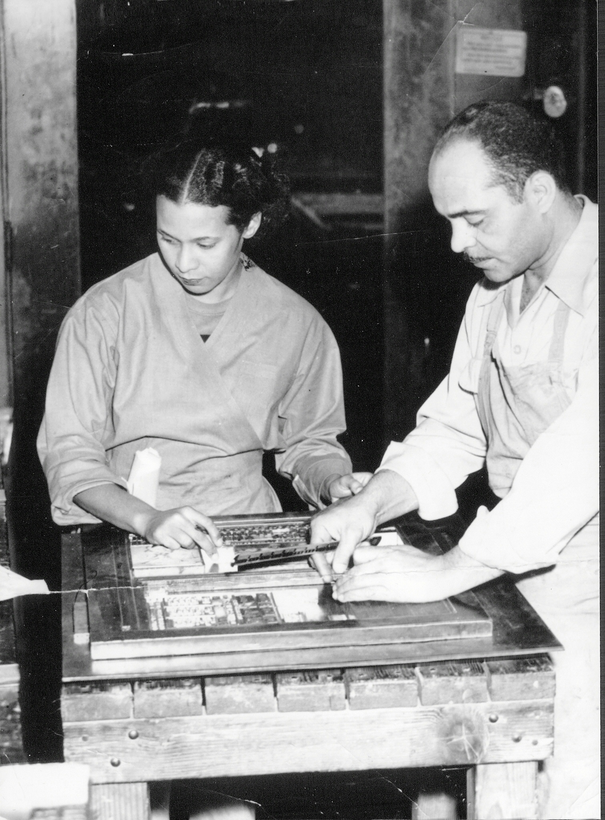 A circa 1950s photo of publishers of the Los Angeles Tribune Lucius and Almena Lomax, parents of Michael Lomax, setting the typeface to print the newspaper.