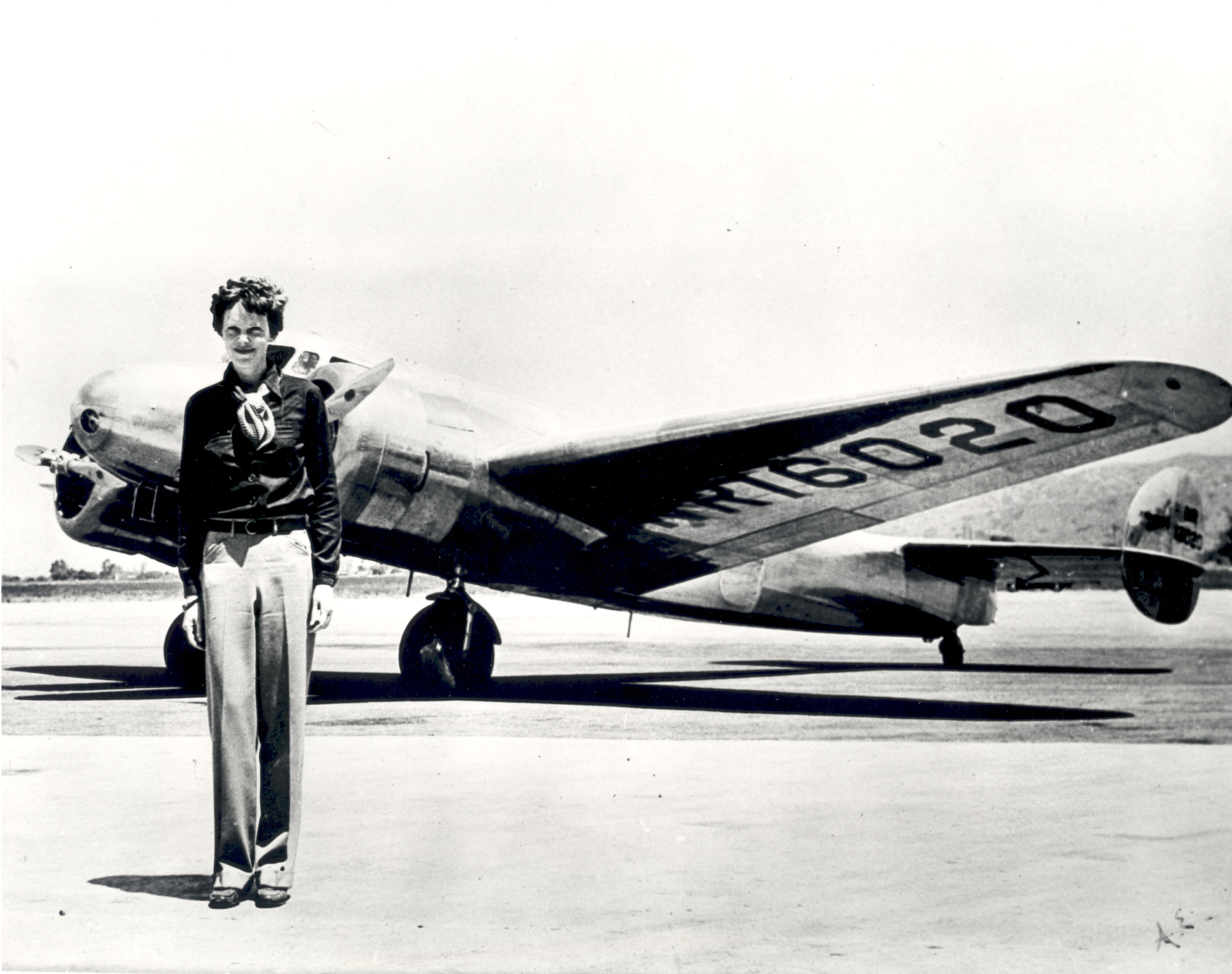 Amelia Earhart standing in front of the Lockheed Electra in which she disappeared in 1937.