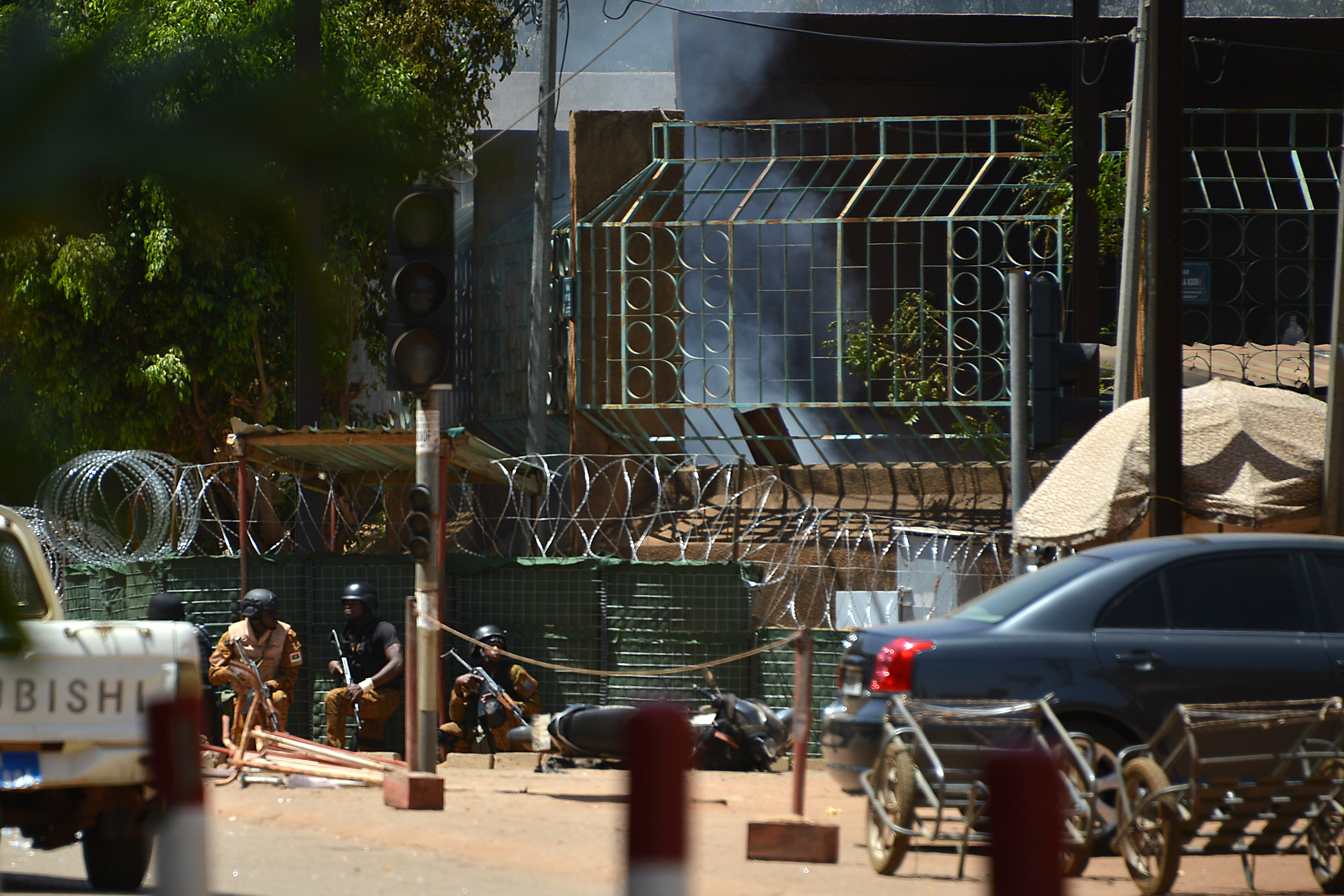 Security personnel take cover as smoke billows from The Institute Francais in Ouagadougou on March 2, 2018, as the capital of Burkina Faso came under multiple attacks targeting the French embassy, the French cultural centre and the country's military headquarters.                 Witnesses said five armed men got out of a car and opened fire on passersby before heading towards the embassy, in the centre of the city. Other witnesses said there was an explosion near the headquarters of the Burkinabe armed forces and the French cultural centre, which are located about a kilometre (half a mile) from the site of the first attack.                  / AFP PHOTO / Ahmed OUOBA        (Photo credit should read AHMED OUOBA/AFP/Getty Images)