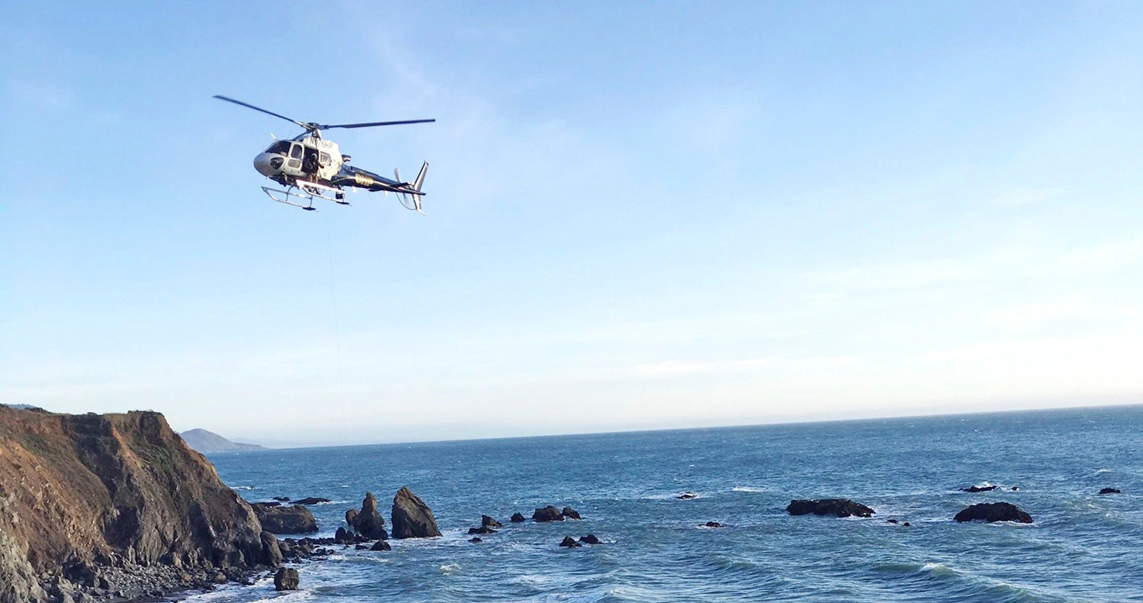 A helicopter hovers over steep coastal cliffs, near Mendocino, Calif., where a vehicle, visible at lower right, plunged about 100 feet off a cliff along Highway 1, killing five passengers.
