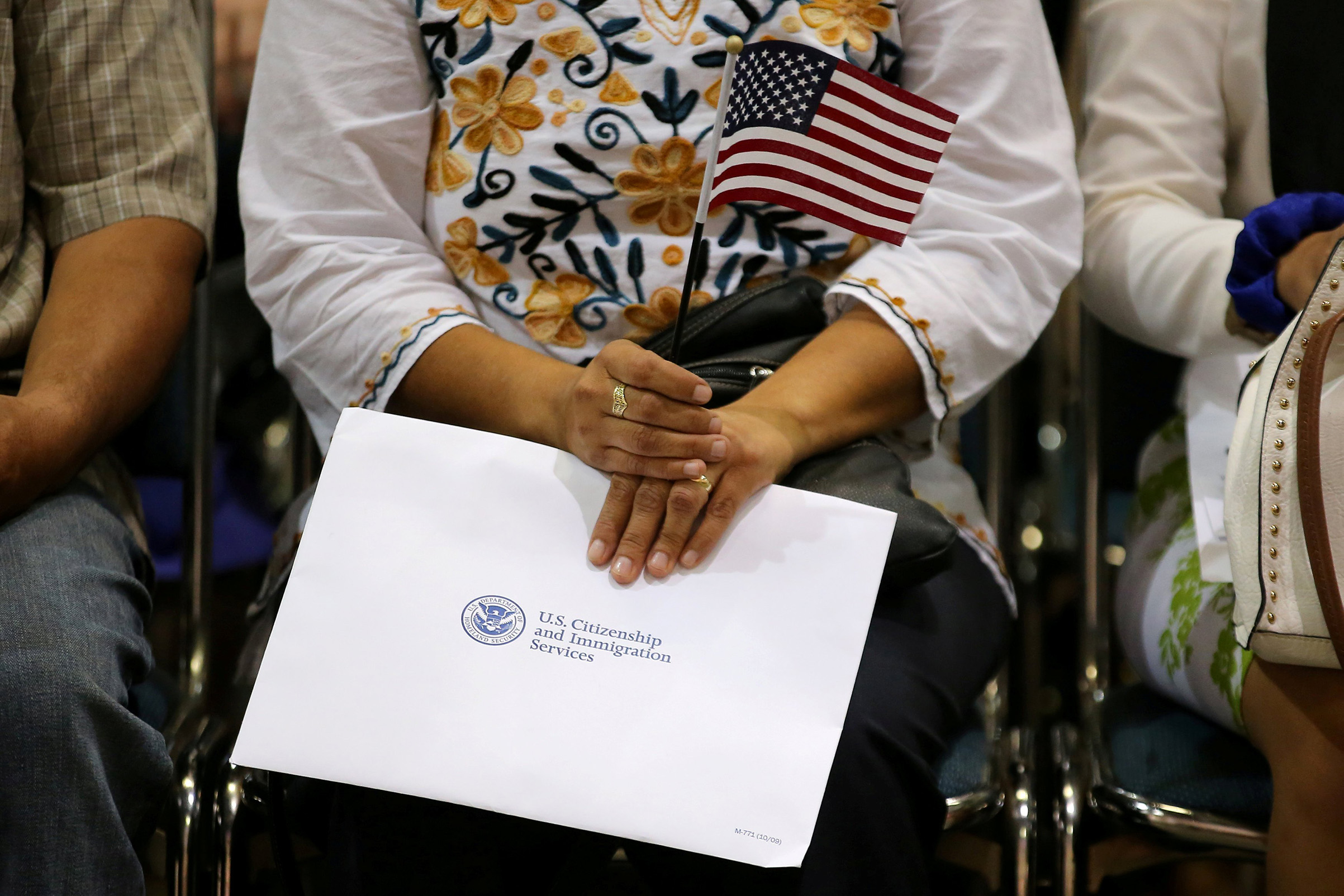 An attendee holds her new country's flag and her naturalization papers as she is sworn in during a U.S. citizenship ceremony in Los Angeles, on July 18, 2017.