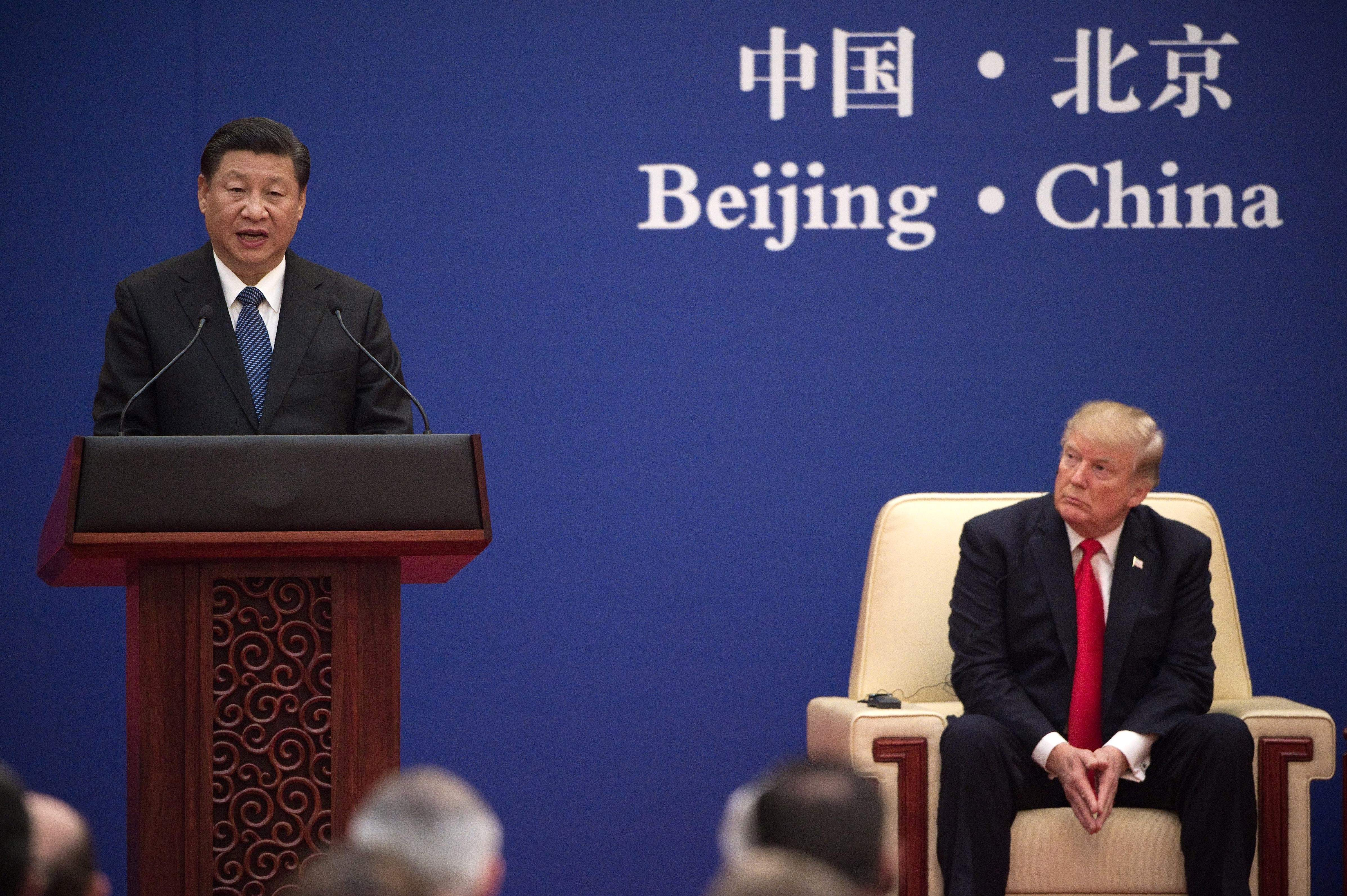 China's President Xi Jinping speaks next to US President Donald Trump during a business leaders event at the Great Hall of the People in Beijing on Nov. 9, 2017.