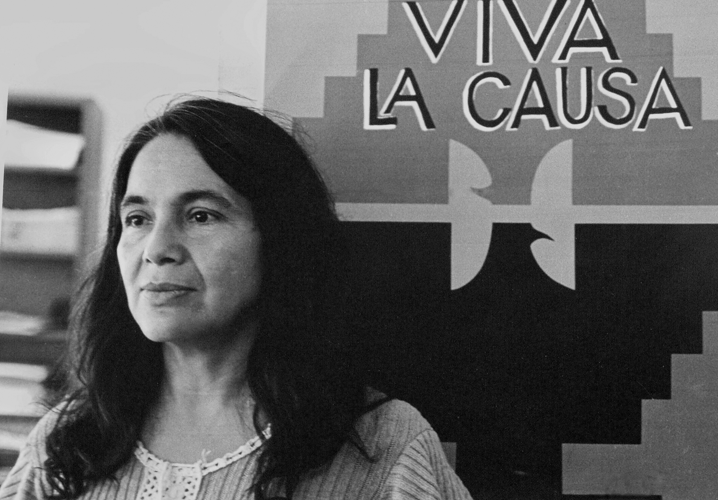 Portrait of labor activist Dolores Huerta, co-founder of the United Farm Workers group, with a union flag that reads 'Viva La Causa,' ca.1970s.