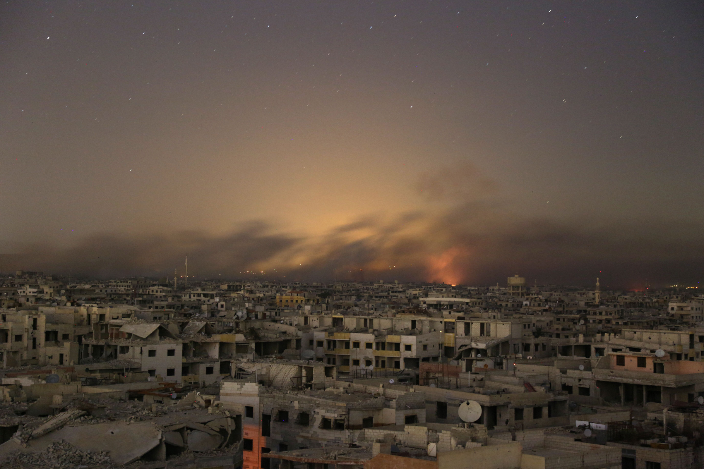 Smoke rises during Syrian government bombardment on the rebel-controlled town of Arbin, in the besieged Eastern Ghouta region on the outskirts of the capital Damascus, on late March 11, 2018.
