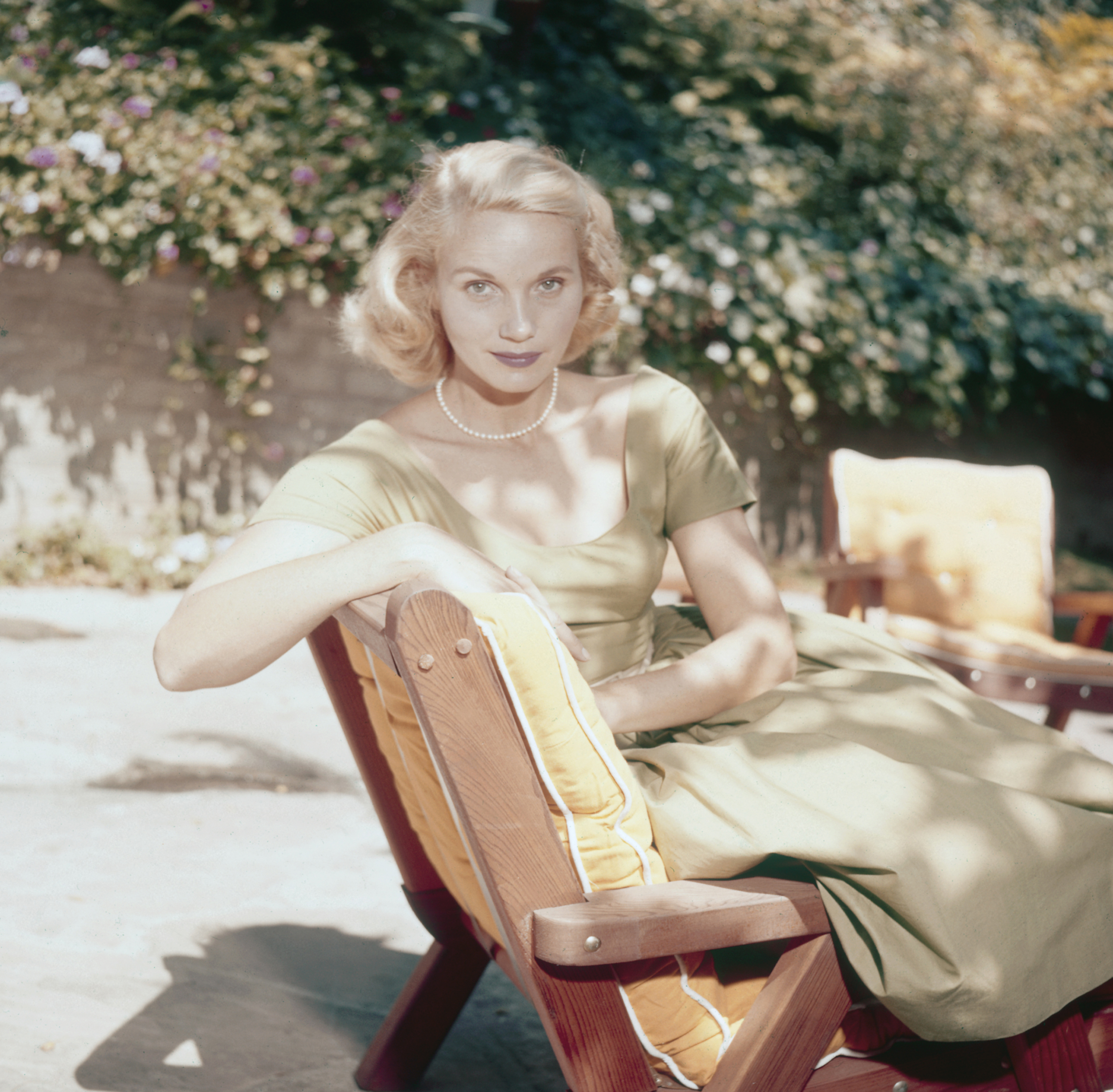 Actress Eva Marie Saint pictured seated on a sun lounger in a garden circa 1950.