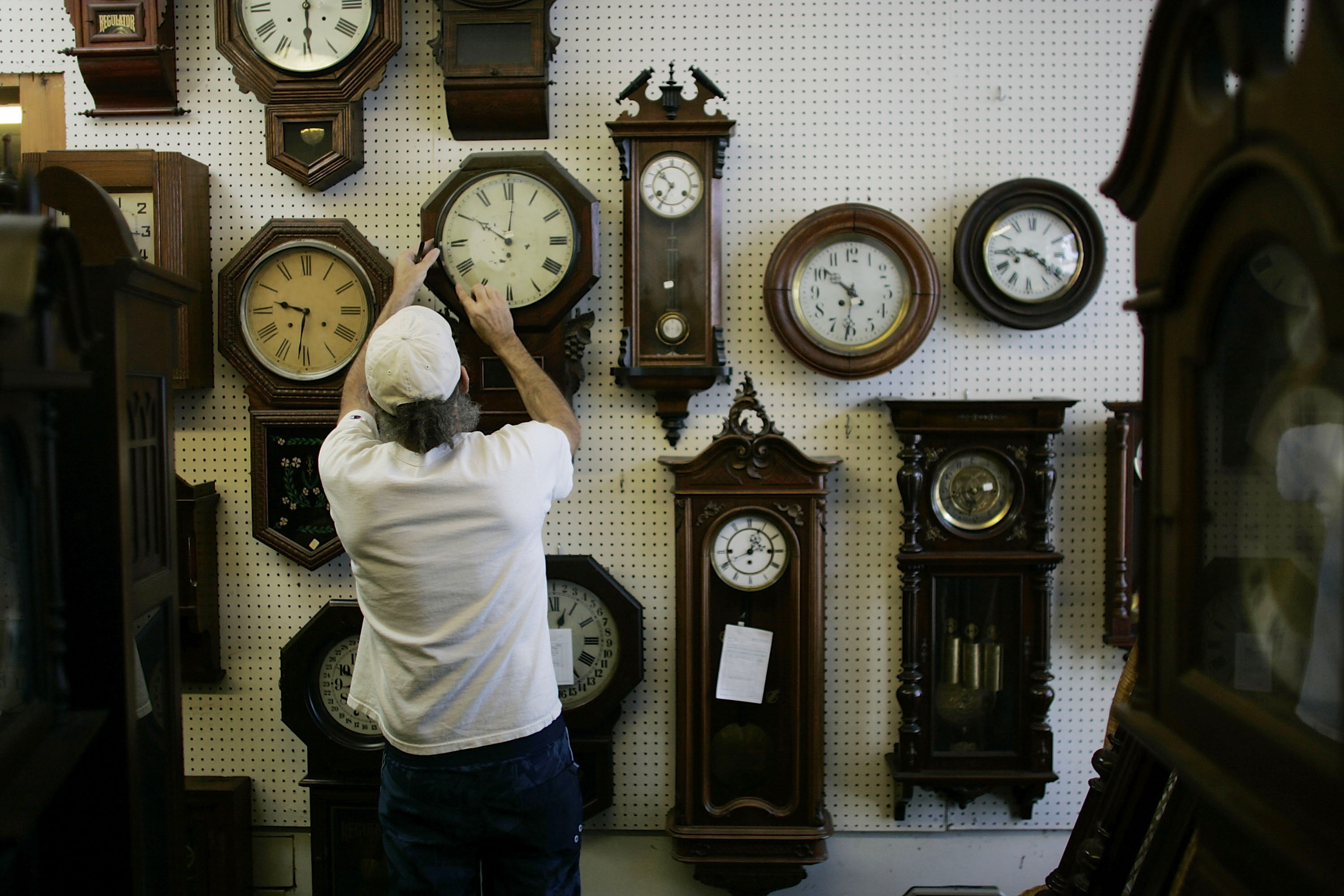 Mark Brown adjusts clocks on the wall at Brown?s Old Time Clock Shop March 6, 2007 in Plantation, Florida. This year day light savings time happens three weeks early and some people fear that it could cause some computer and gadget glitches.